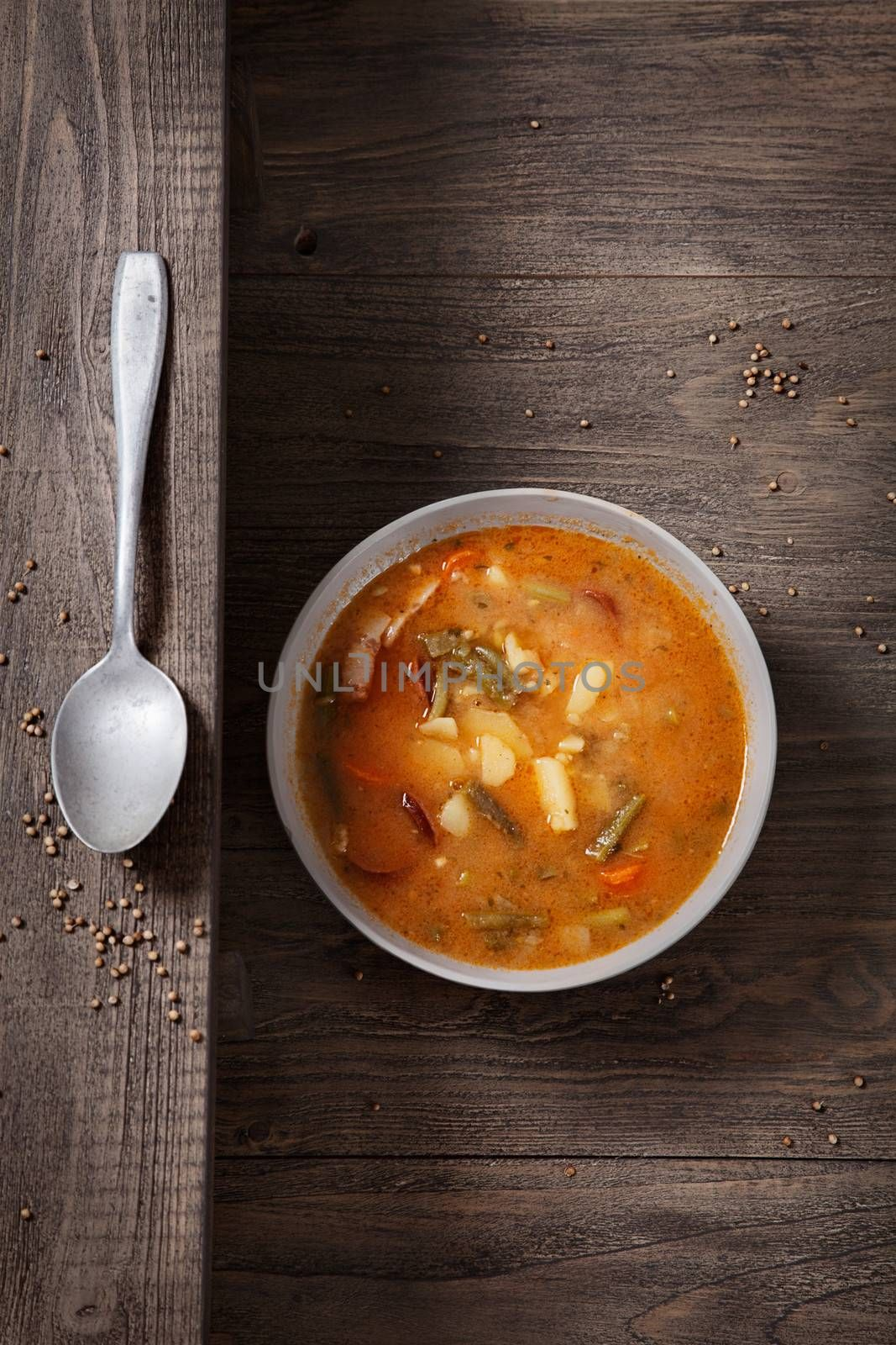 Delicious vegetable stew soup with sausage and french beans on wood.