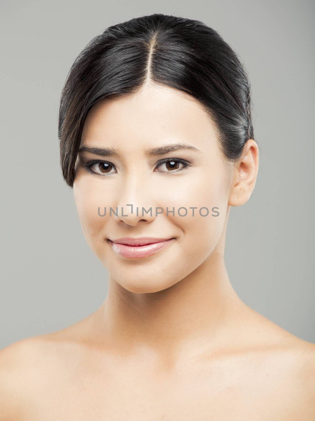 Beauty portrait of young asian woman smiling, over a gray background.