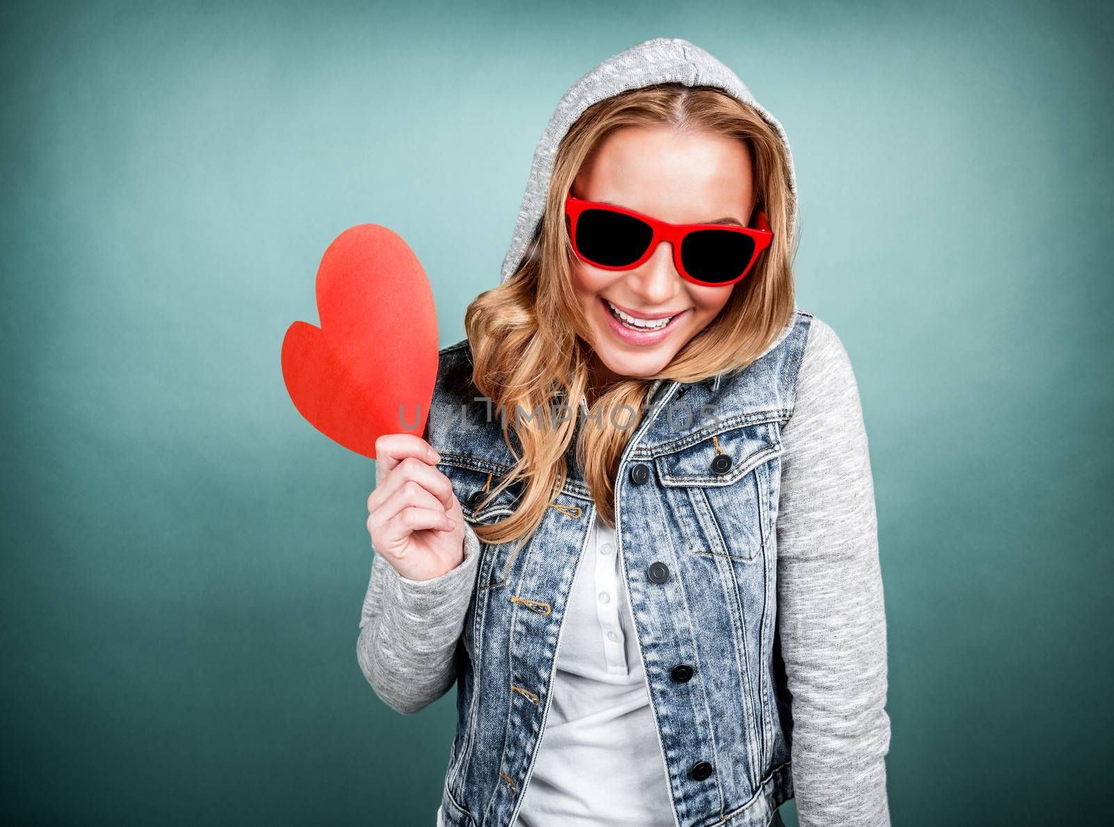 Happy romantic girl laughing on blue background, wearing stylish jacket with hood and sunglasses, holding red heart-shaped Valentine day card