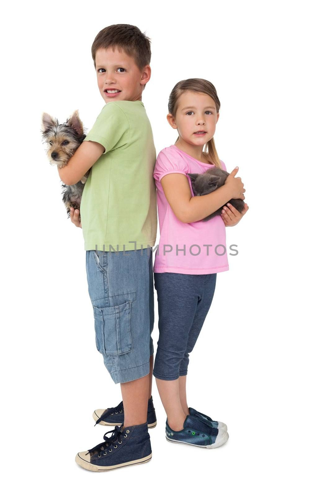 Siblings holding their pets and smiling at camera on white background