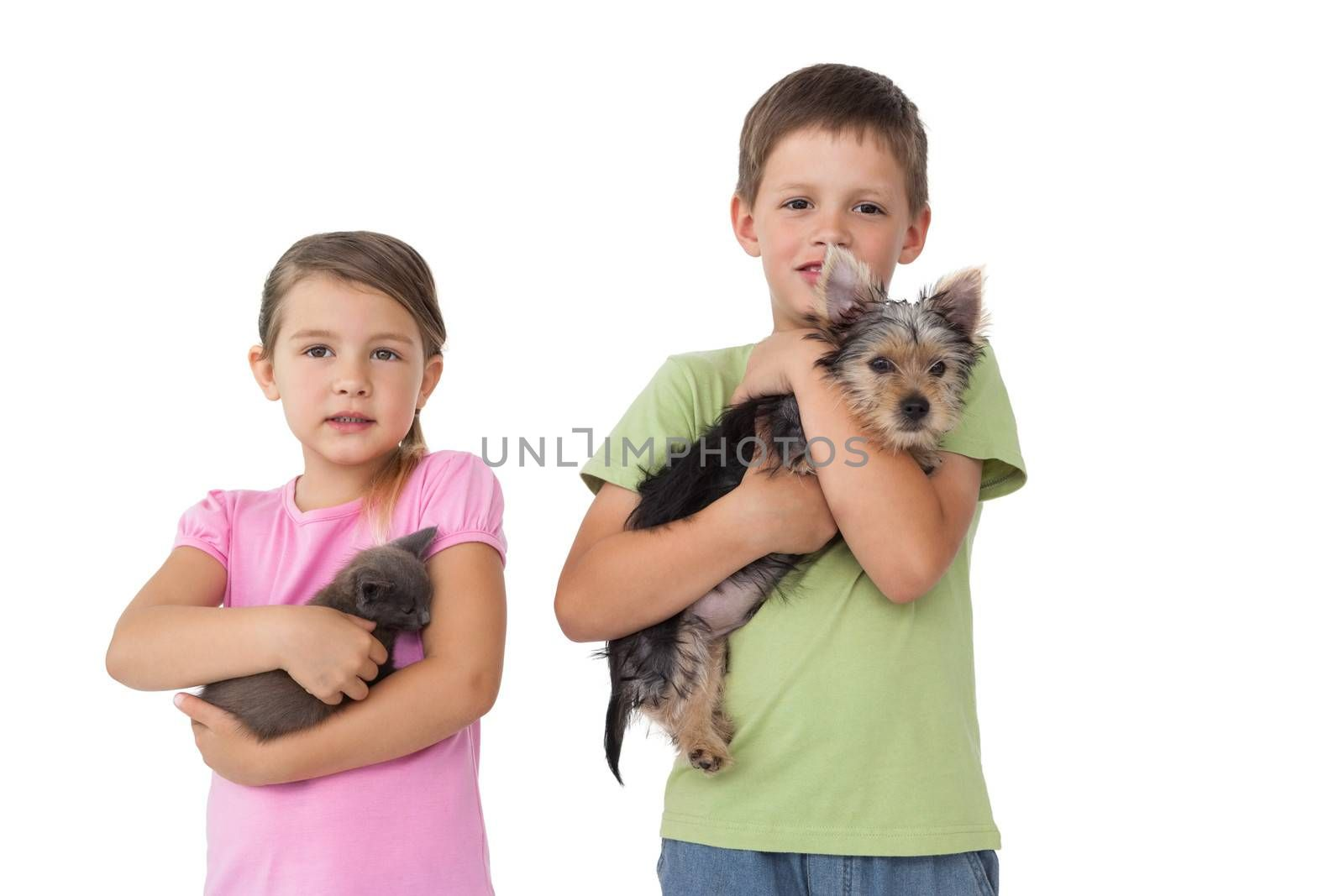 Cute siblings holding their pets and smiling at camera on white background