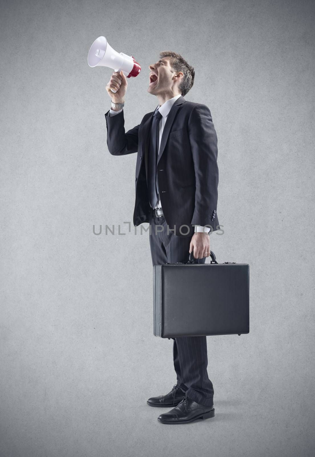 A young Businessman Shouting Through Megaphone