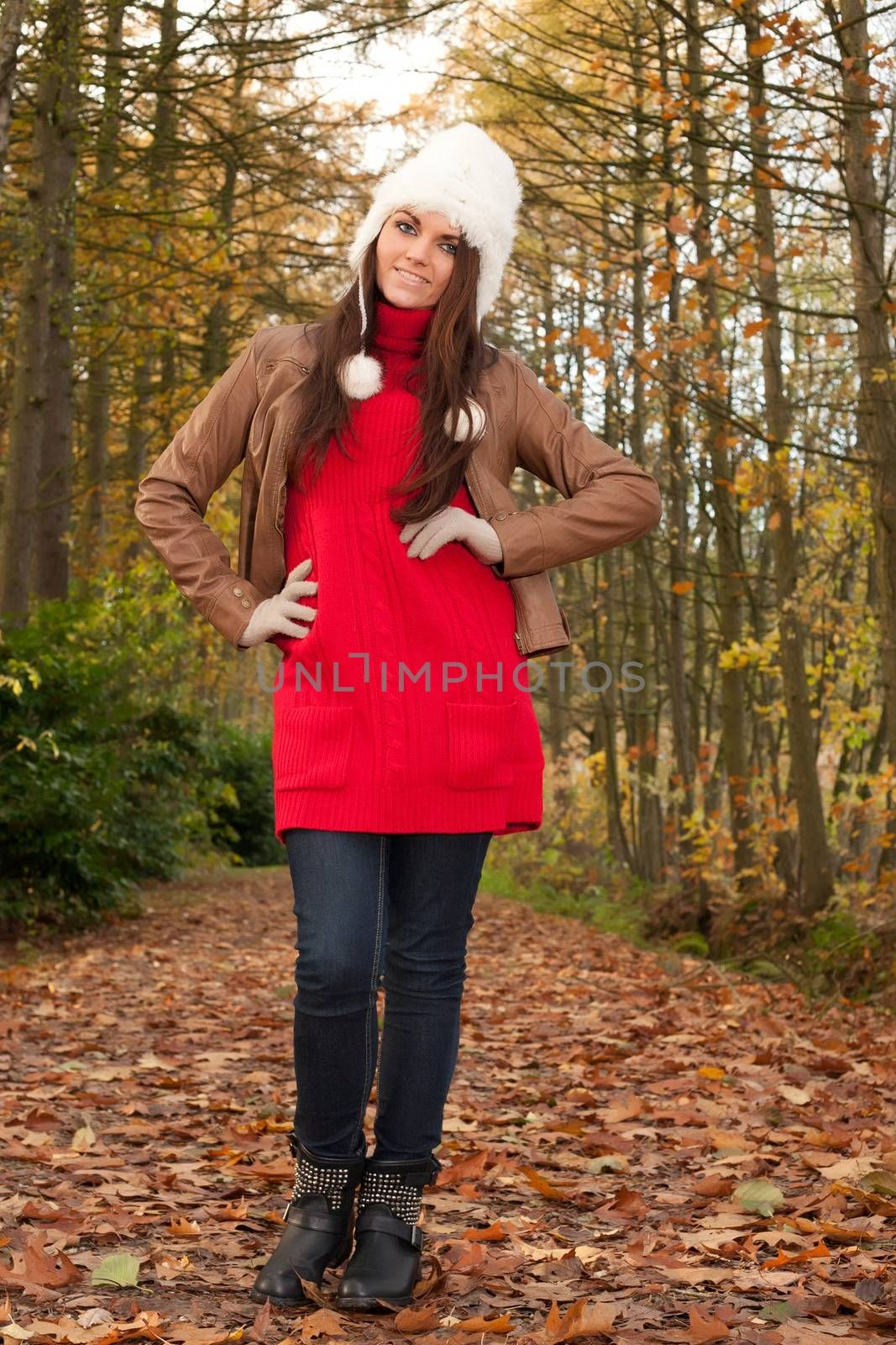 Happy brunette is having a nice time in the park while it's autumn