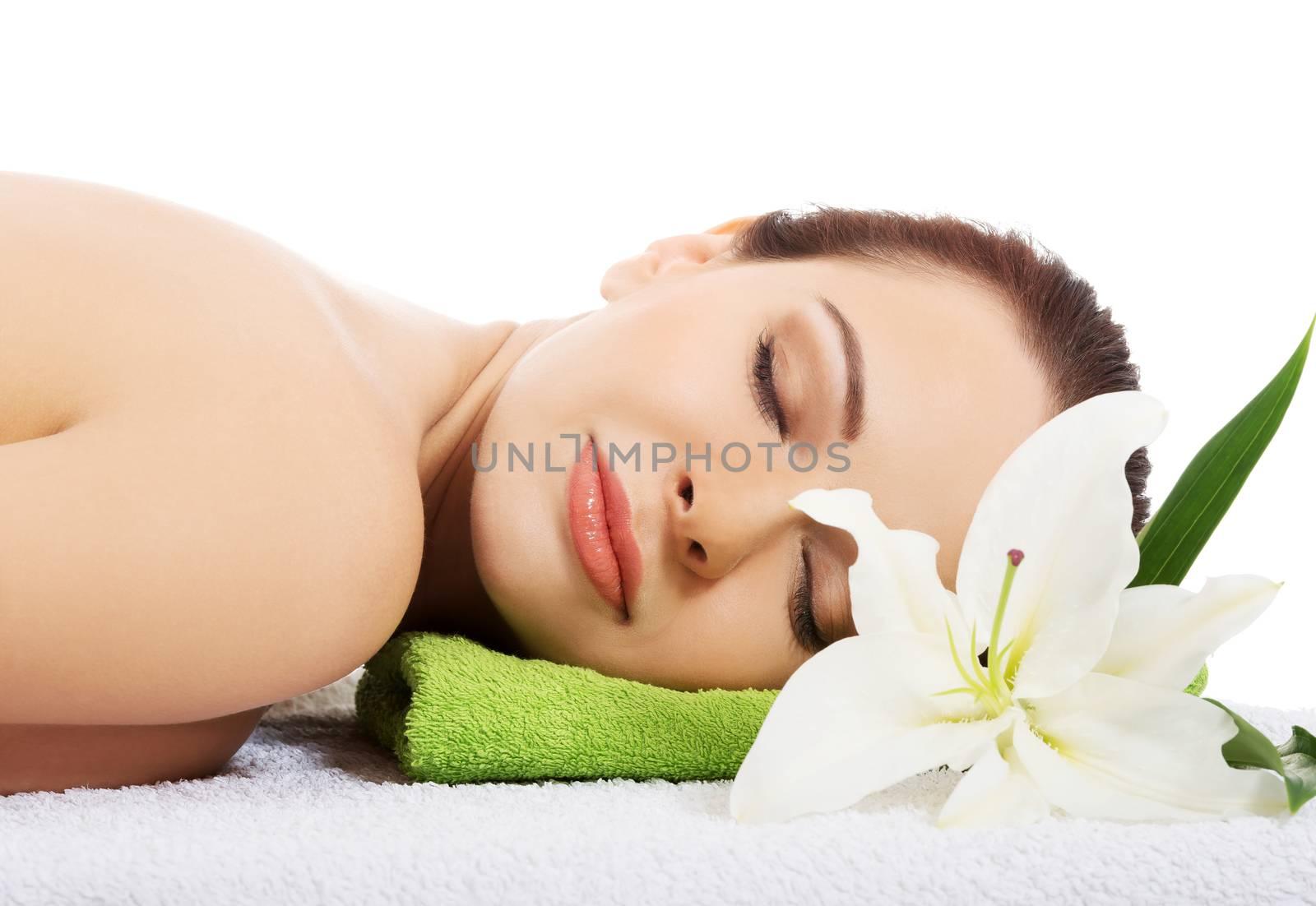 Beautiful woman lying at spa salon.