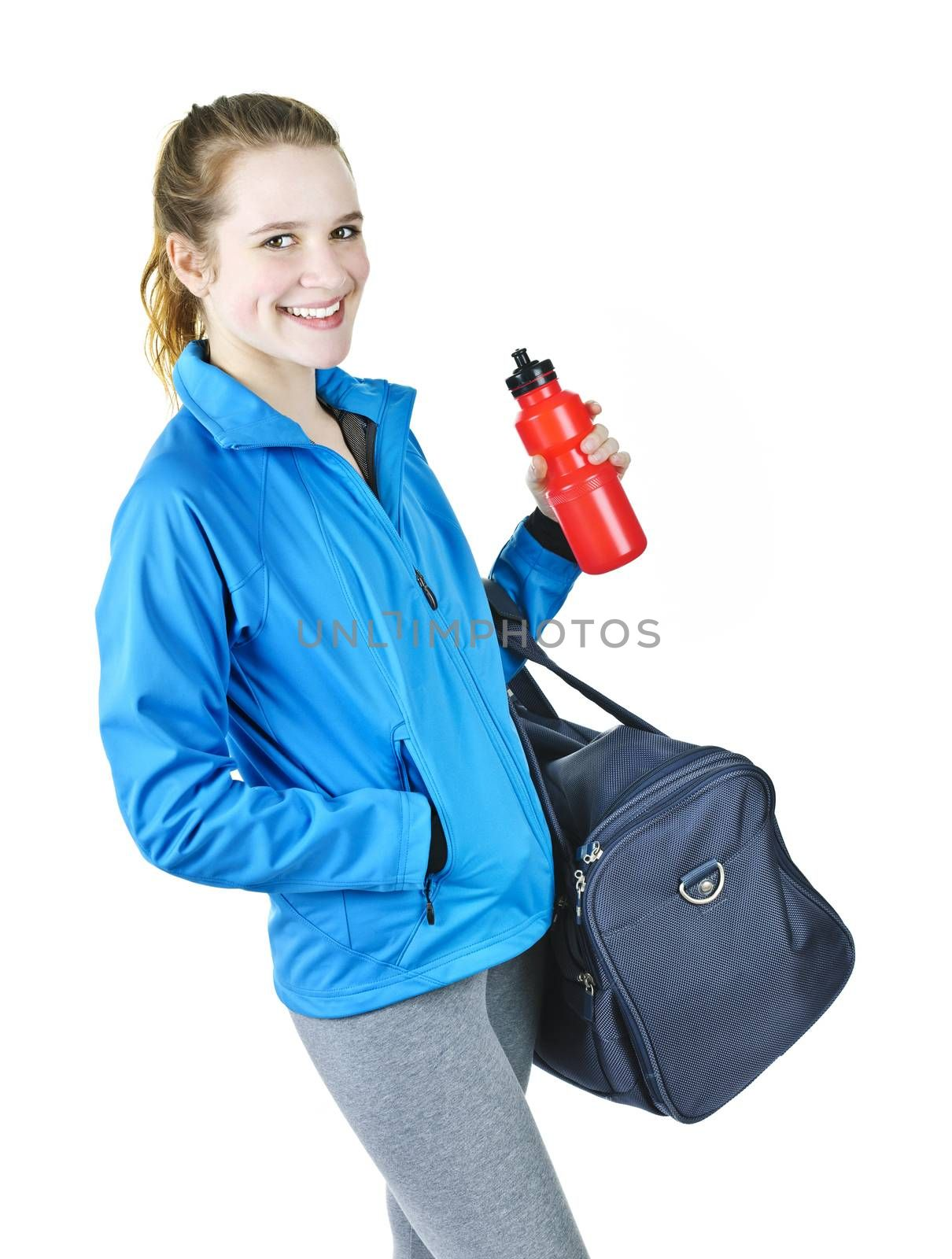 Smiling fit young woman with gym bag and water bottle ready for fitness exercise