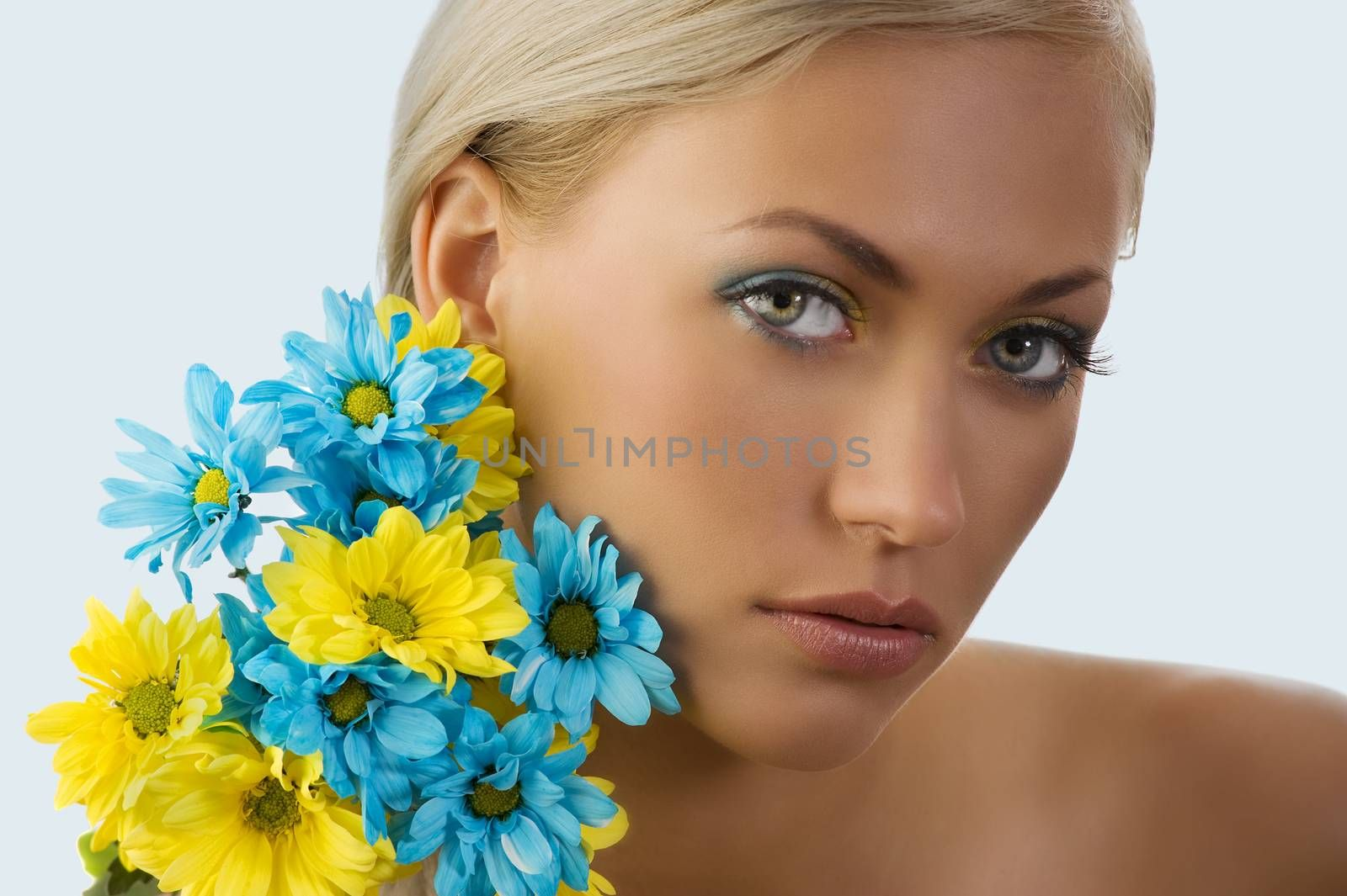 beauty portrait of pretty young blond girl with blue and yellow daisy near her face