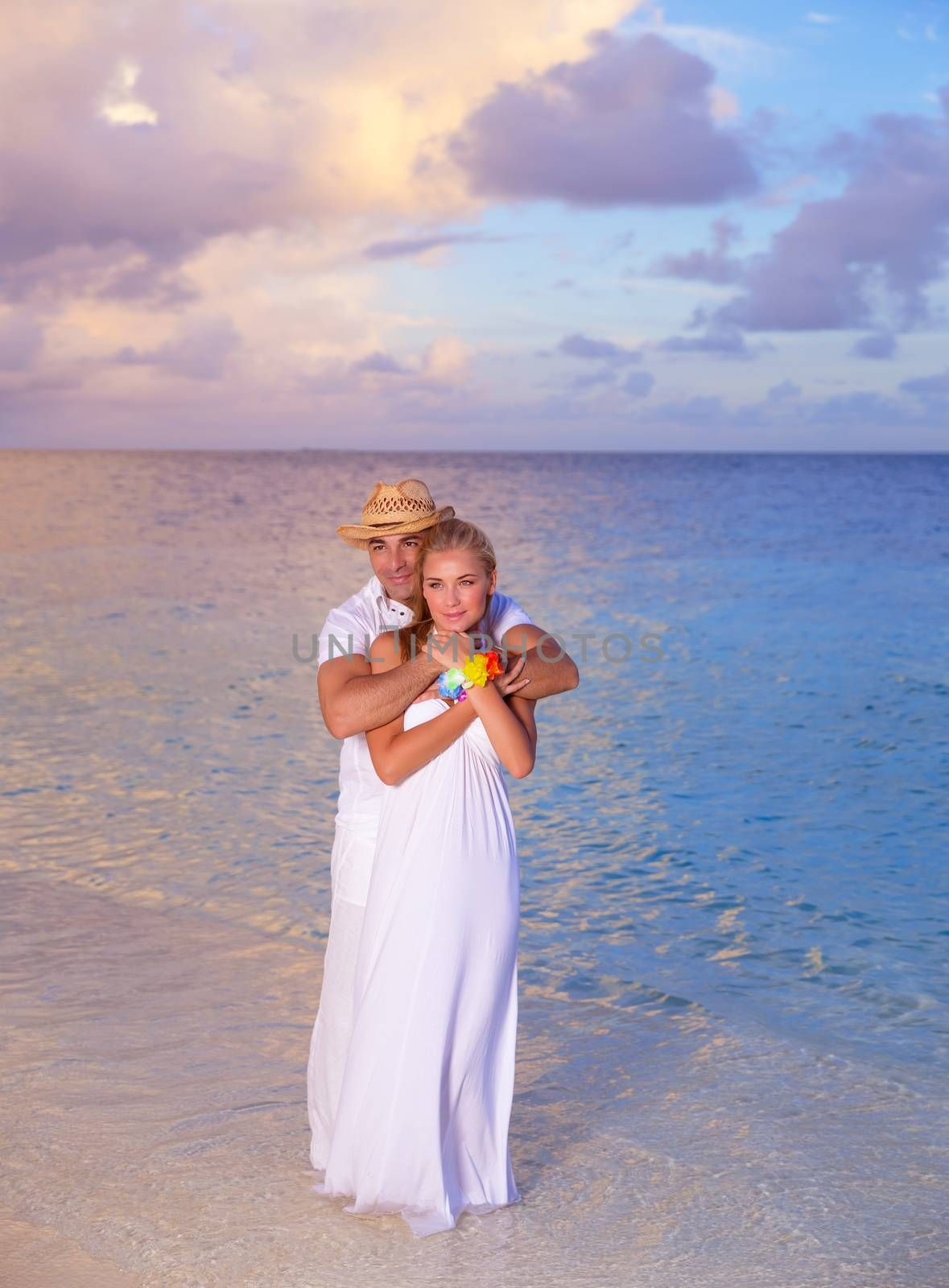 Beautiful couple relaxing on the beach in the evening, romantic date on seashore, spending honeymoon on Maldives