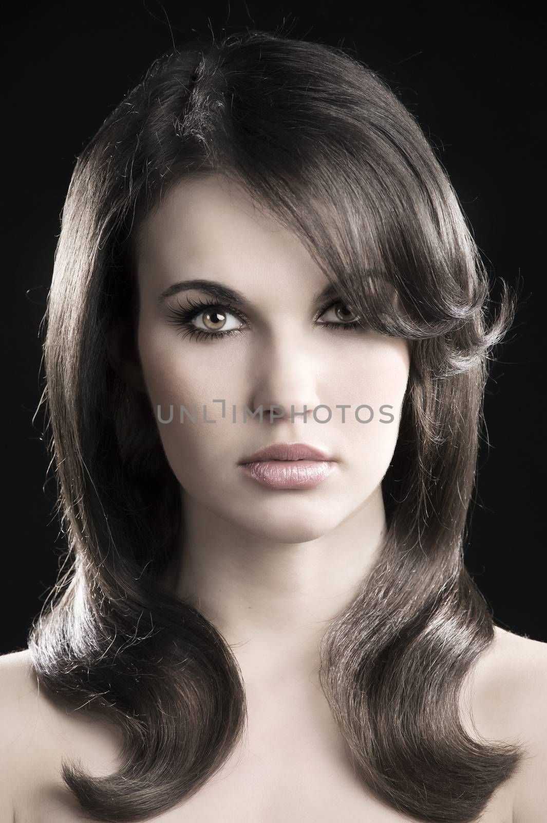 desaturated fashion portrait of beautiful sensual woman with elegant hairstyle over black background