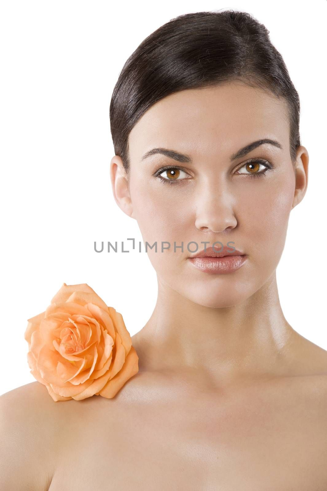 fresh portrait of a young brunette woman wiith color flower near the her face
