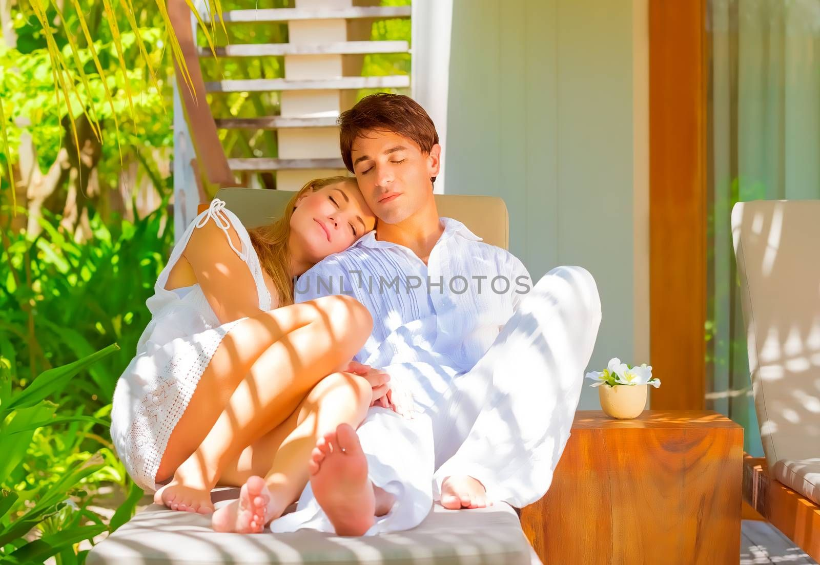 Portrait of happy couple sitting and hugging outdoors with eyes closed in pleasure, spending summer holidays on paradise beach