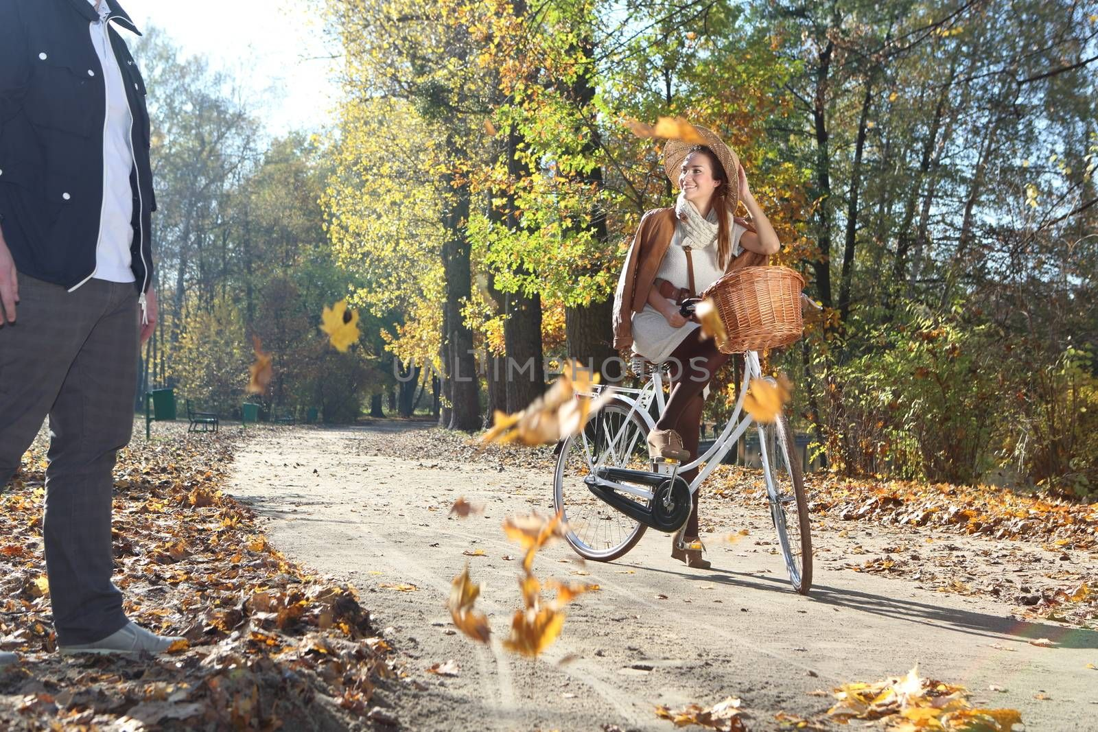 girl on a bicycle in a park alley background color of autumn leaves