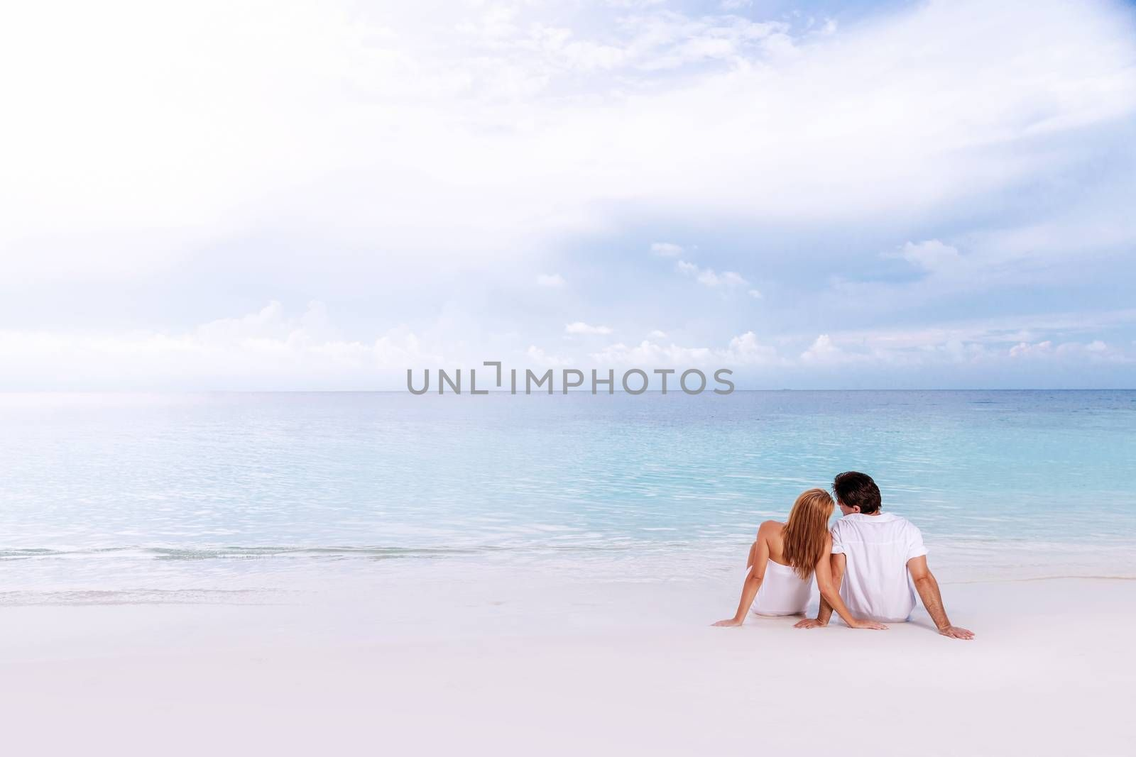 Romantic couple sitting on the beach and enjoying beautiful seaview, side view, spending time together, summer vacation concept