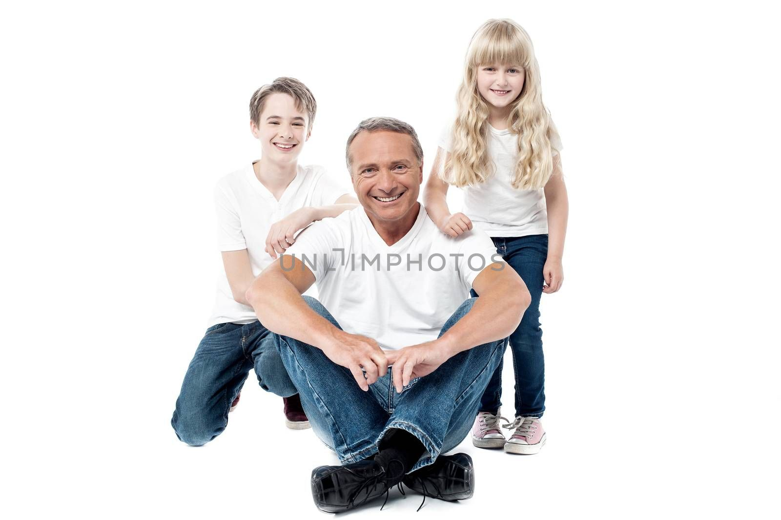 Happy father posing to the camera with his son and daughter