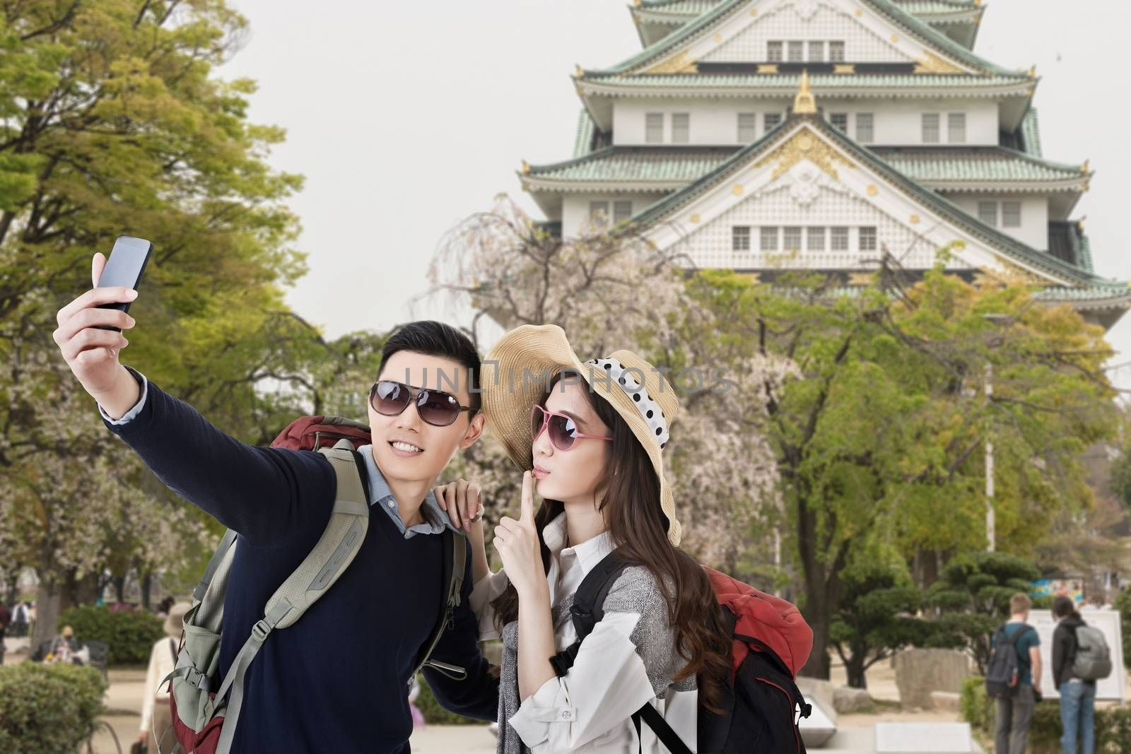 Asian couple travel and selfie in castle at Osaka, Japan.
