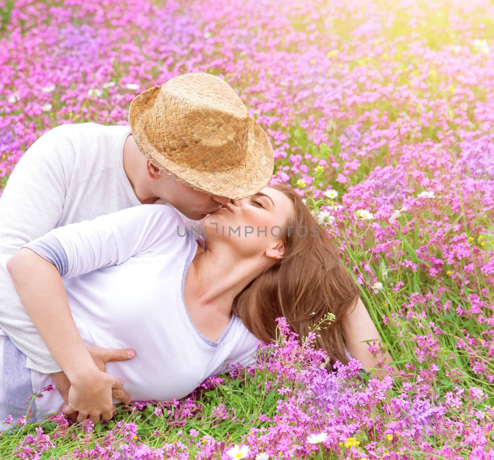 Romantic kisses outdoors, attractive man kissing his beautiful young wife lying down on pink floral meadow, spring time concept