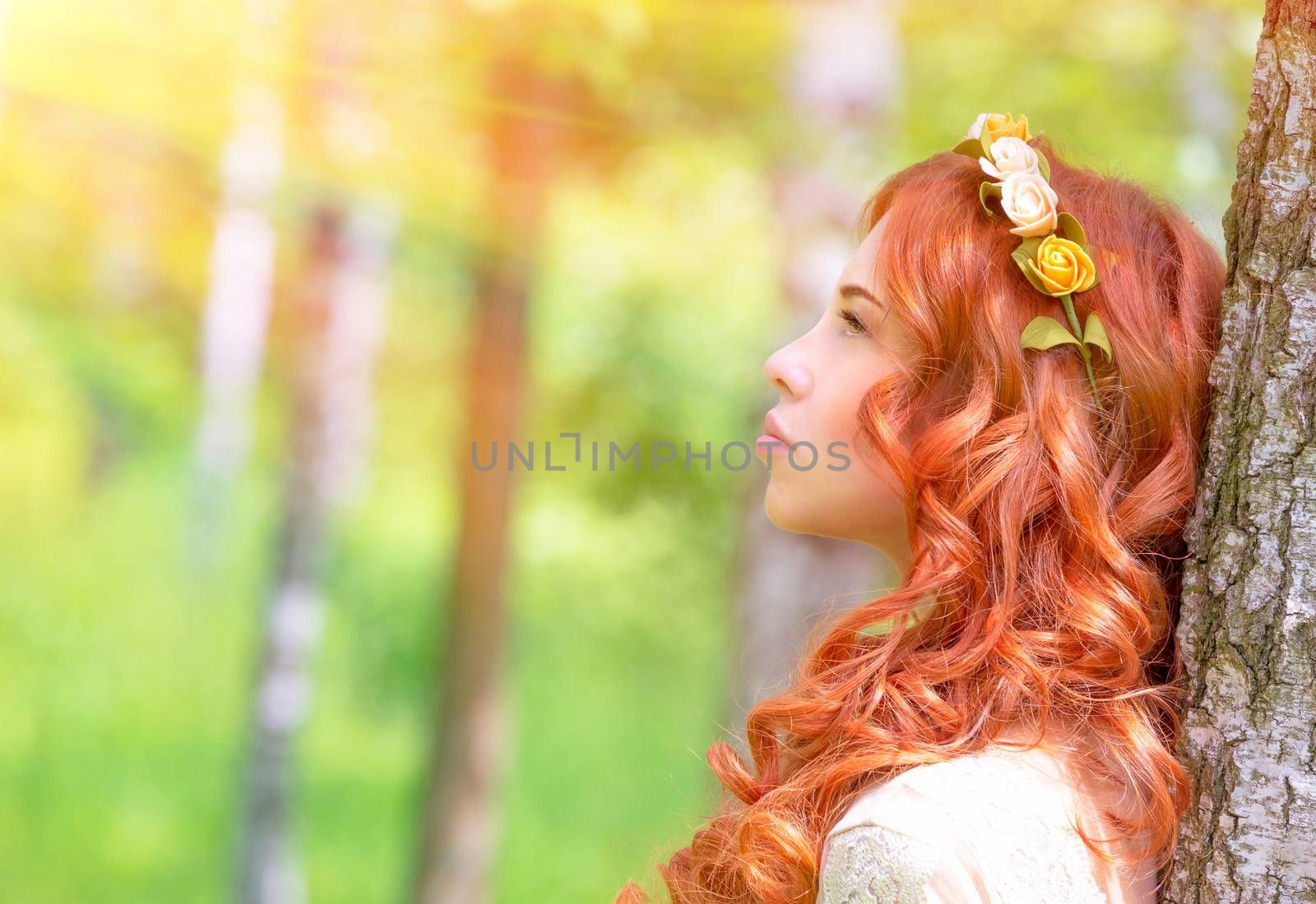 Side view of cute romantic woman looking on sun rays, wearing gentle wreath on curly red hair, fashionable photoshoot in the park