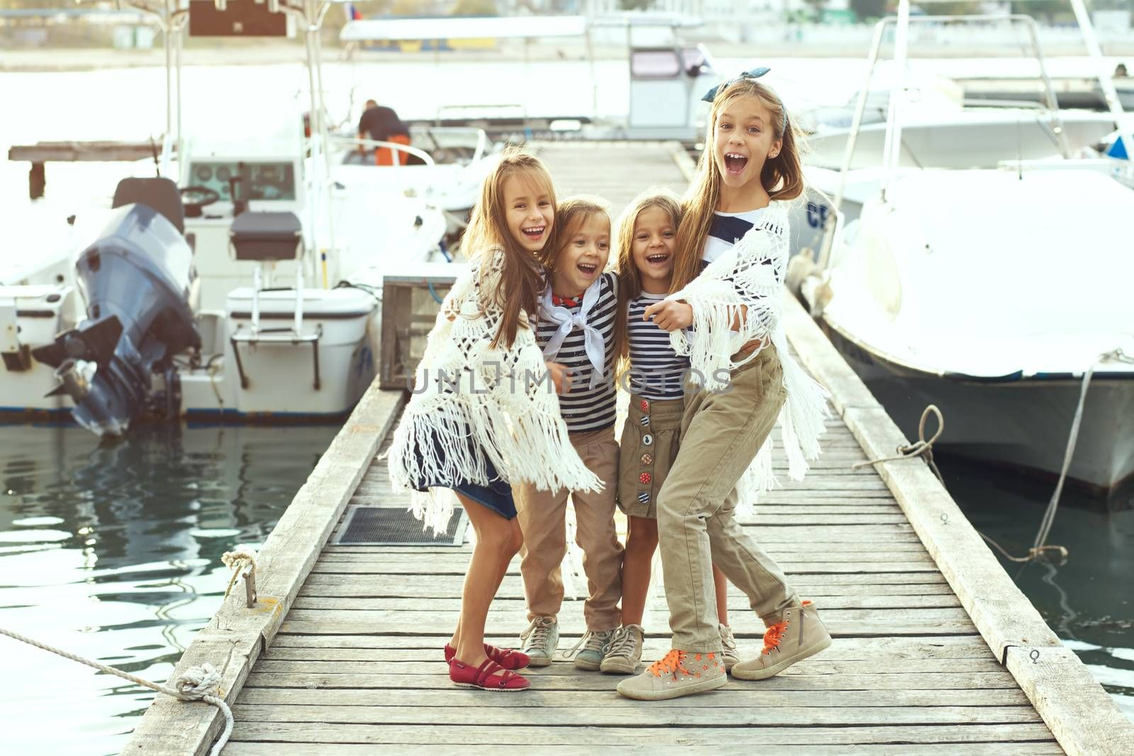 Group of fashion kids wearing navy clothes in marine style having fun in the sea port