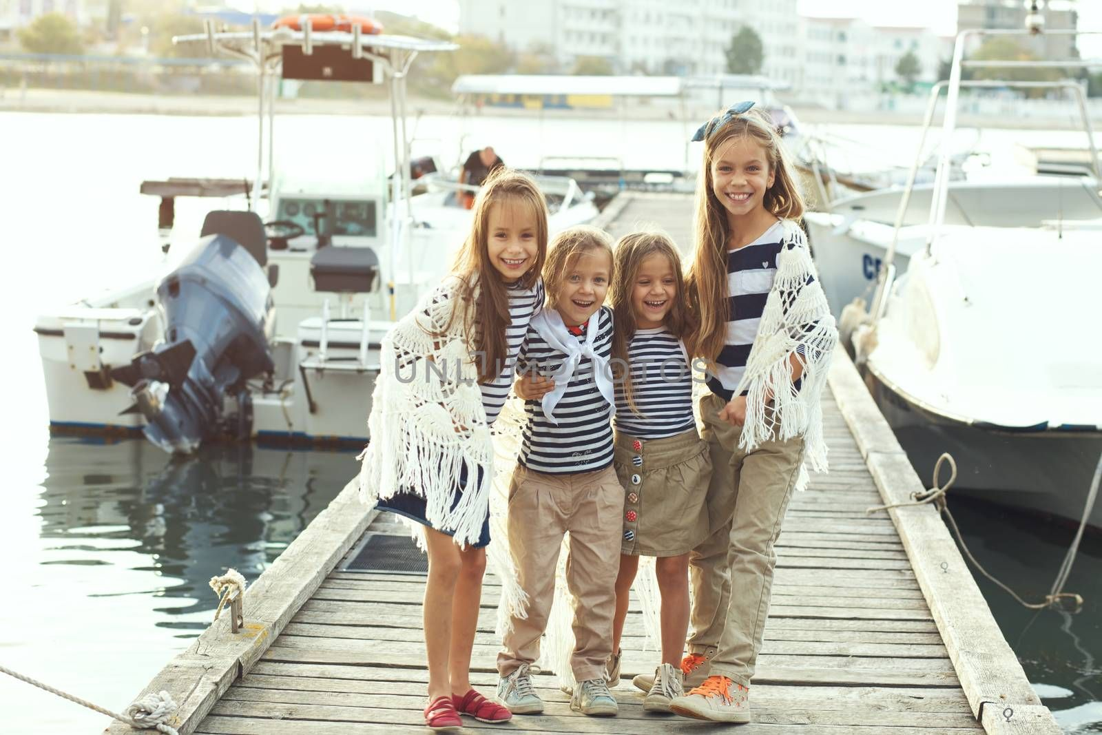 Group of fashion kids wearing navy clothes in marine style walking in the sea port