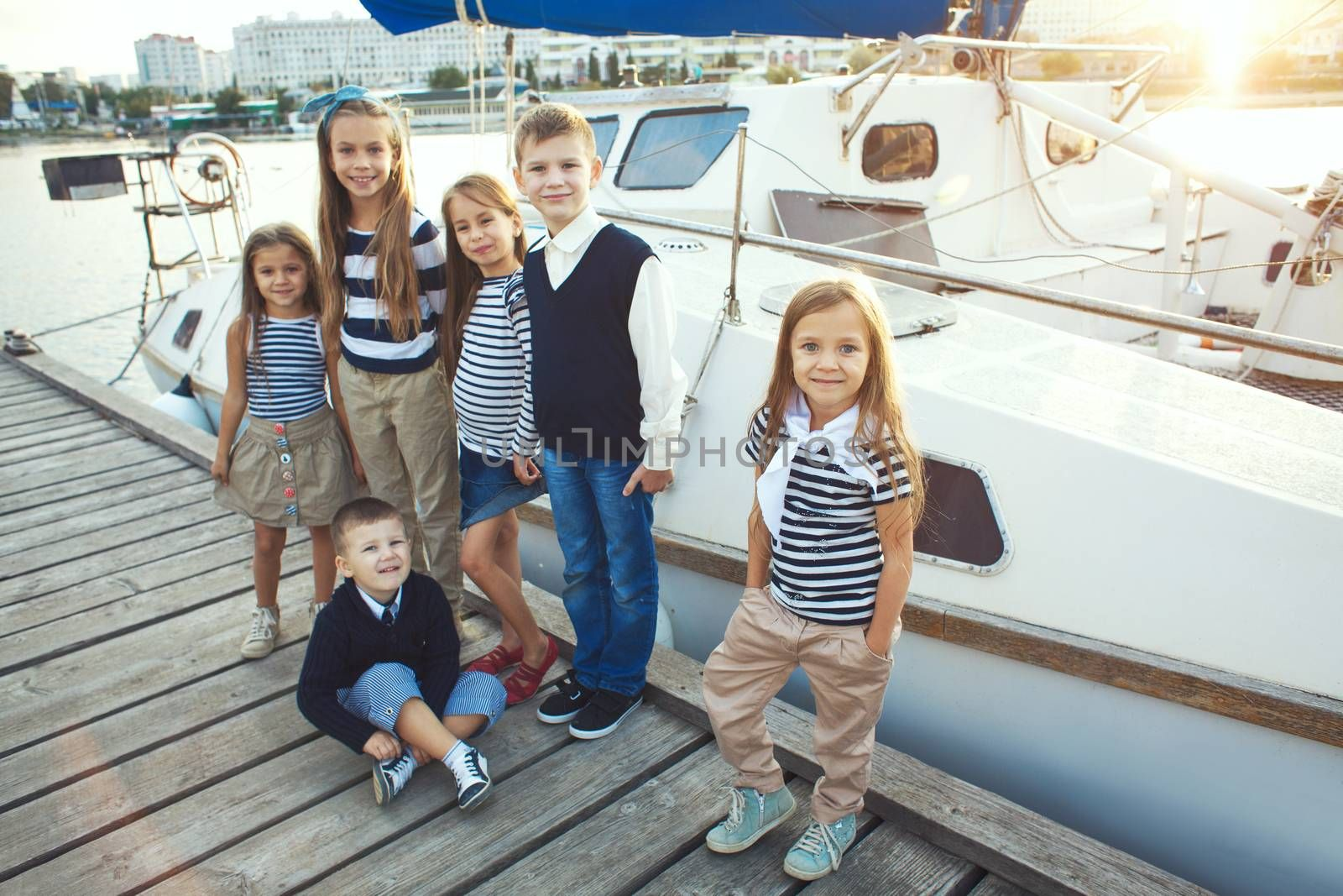Many fashion kids models wearing navy clothes in marine style walking in the sea port near white fashionable yacht
