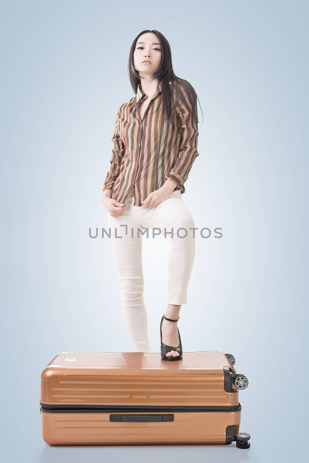 Modern Asian woman stand on a luggage.