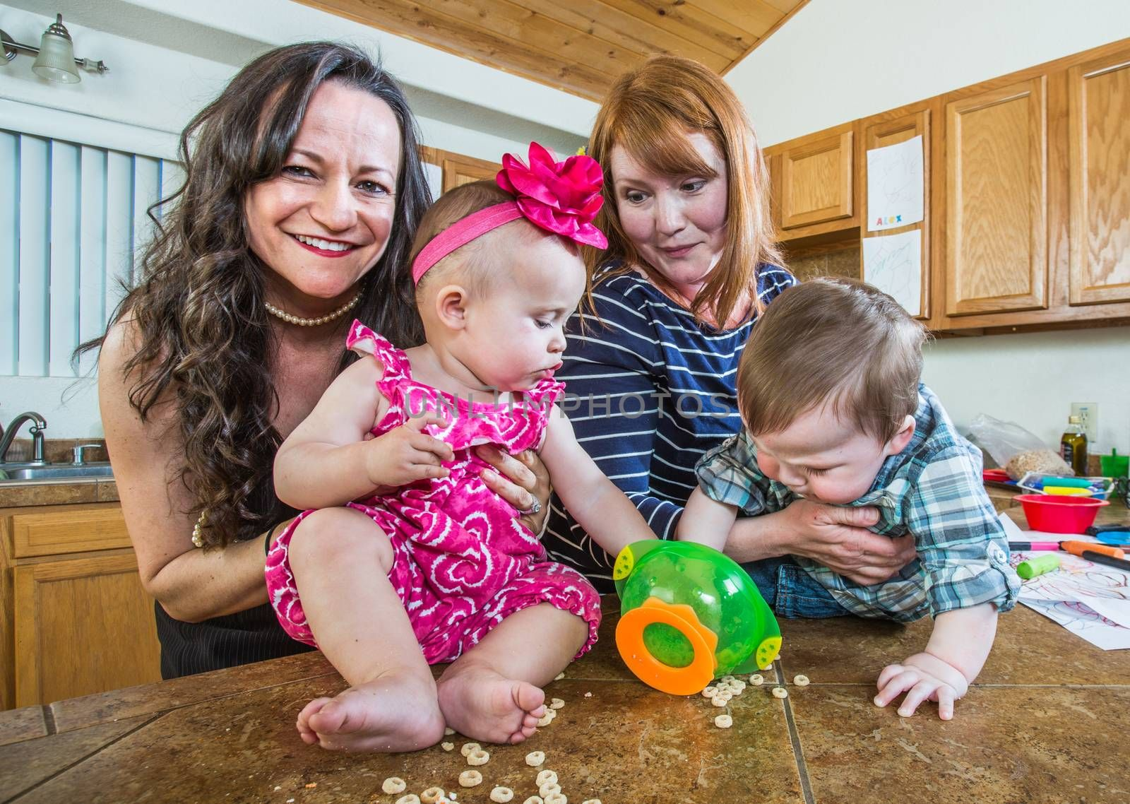 Mothers in kitchen play with their babies