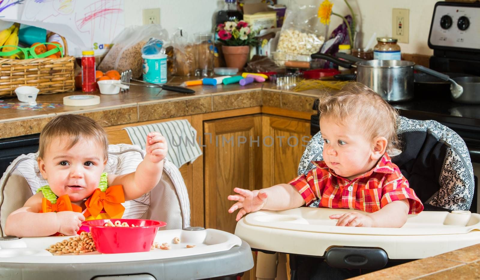 Two babies eating breakfast together in highchairs