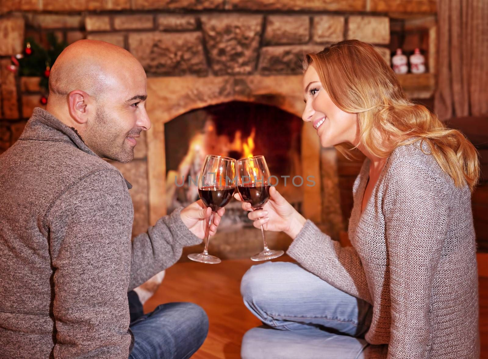Side view of happy cheerful couple sitting on the floor near fireplace, clinking glasses with tasty red wine, enjoying romantic date