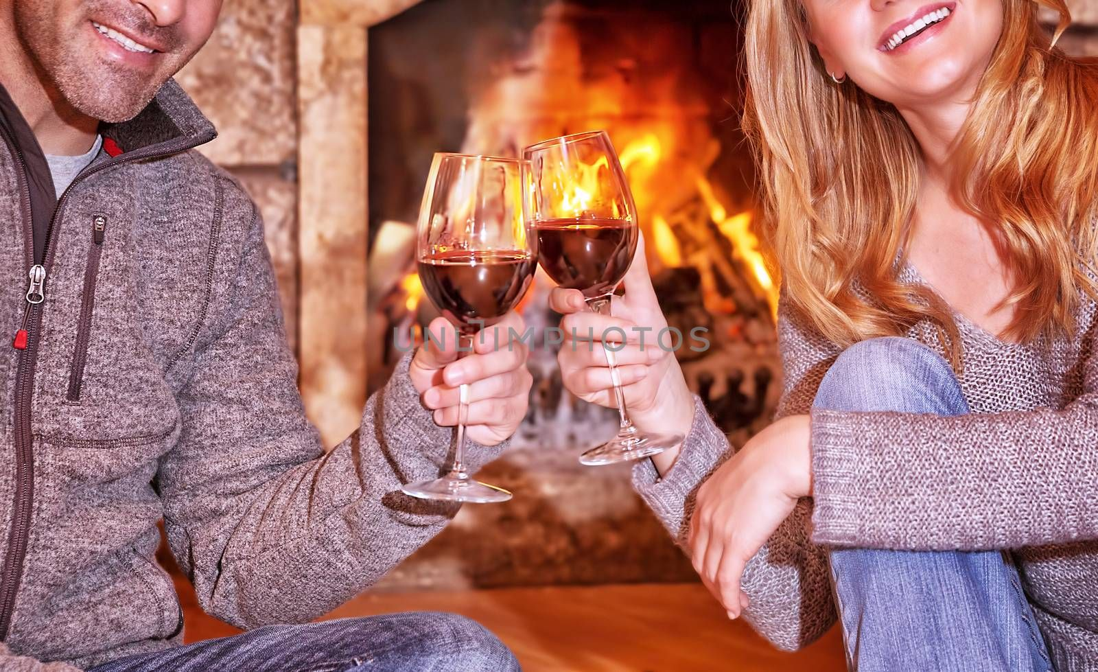 Happy young couple sitting near fireplace and drinking wine, enjoying romantic date, celebrating Valentines day in a cozy winter house