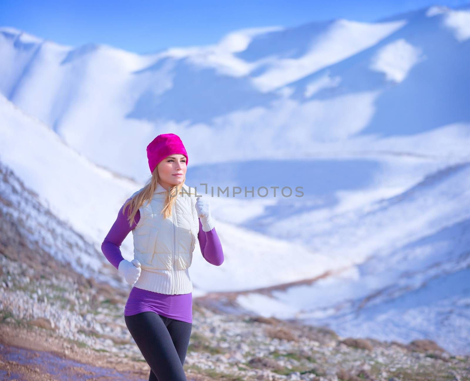Jogging outdoors, cute sportive woman running along mountains covered with snow, workout in winter time, active lifestyle concept