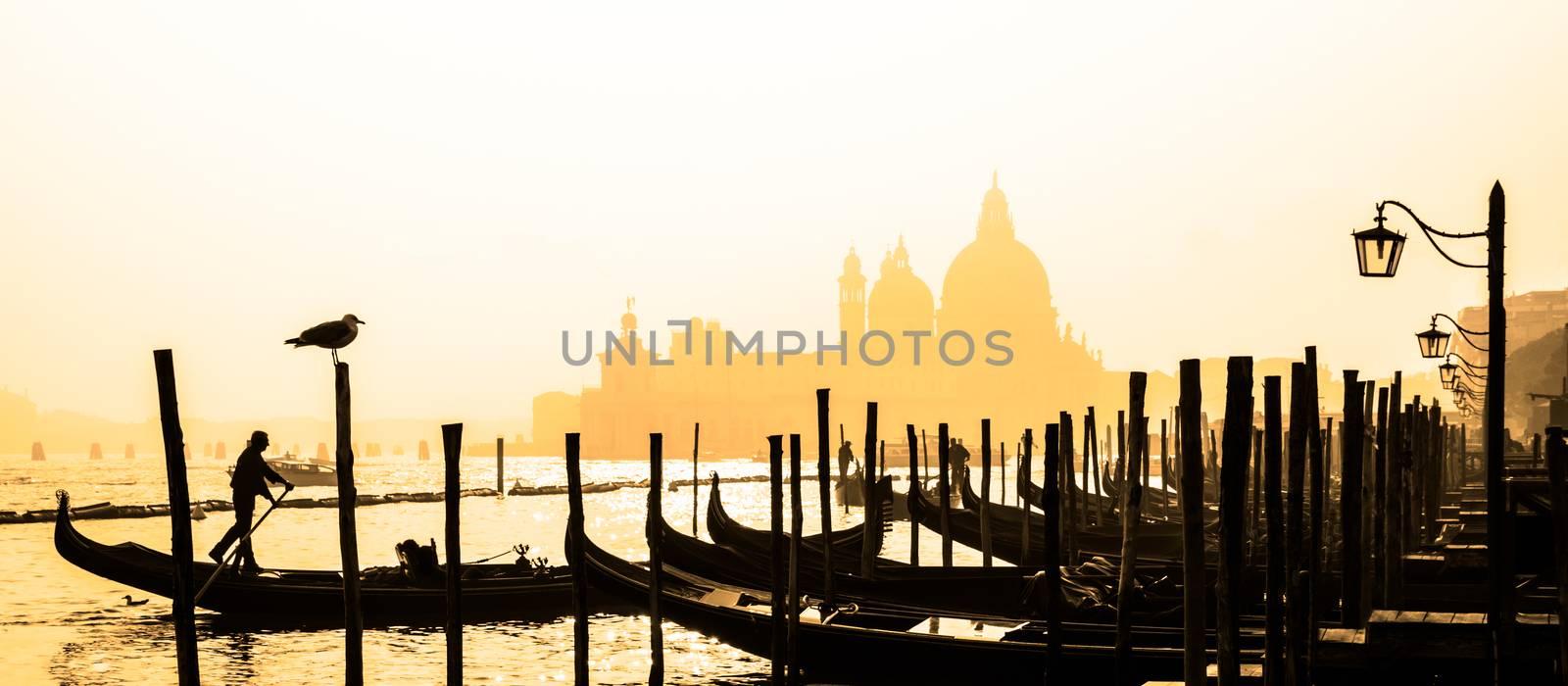Romantic Italian city of Venice, a World Heritage Site: traditional Venetian wooden boats, gondolier and Roman Catholic church Basilica di Santa Maria della Salute in the misty background.