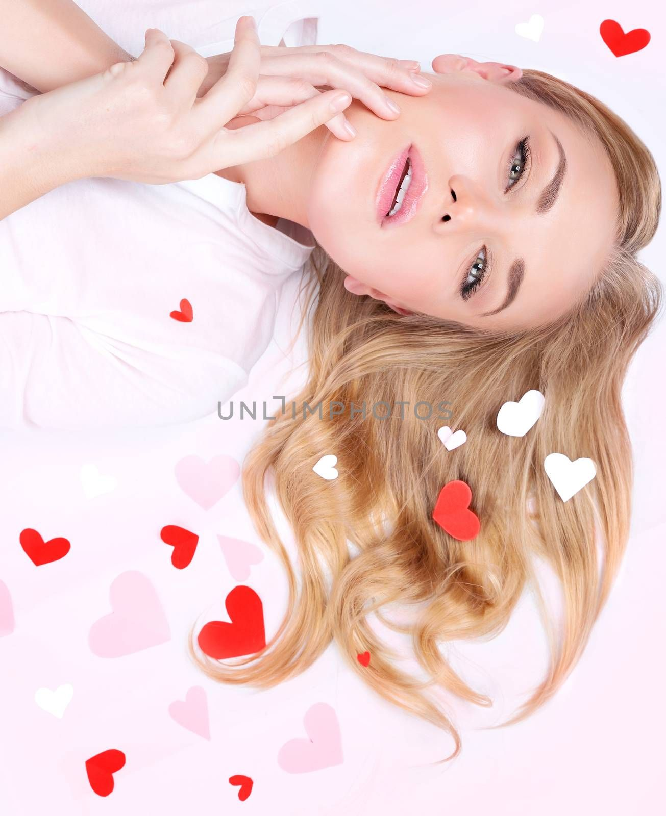 Closeup portrait of a beautiful romantic woman lying down on pink background, many little red hearts on blond hair, Valentines day concept