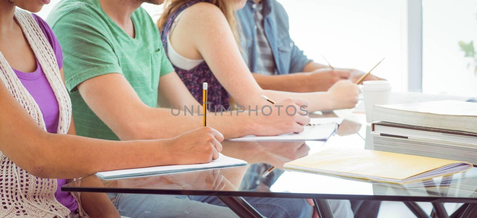 Fashion students writing on notepad at the college