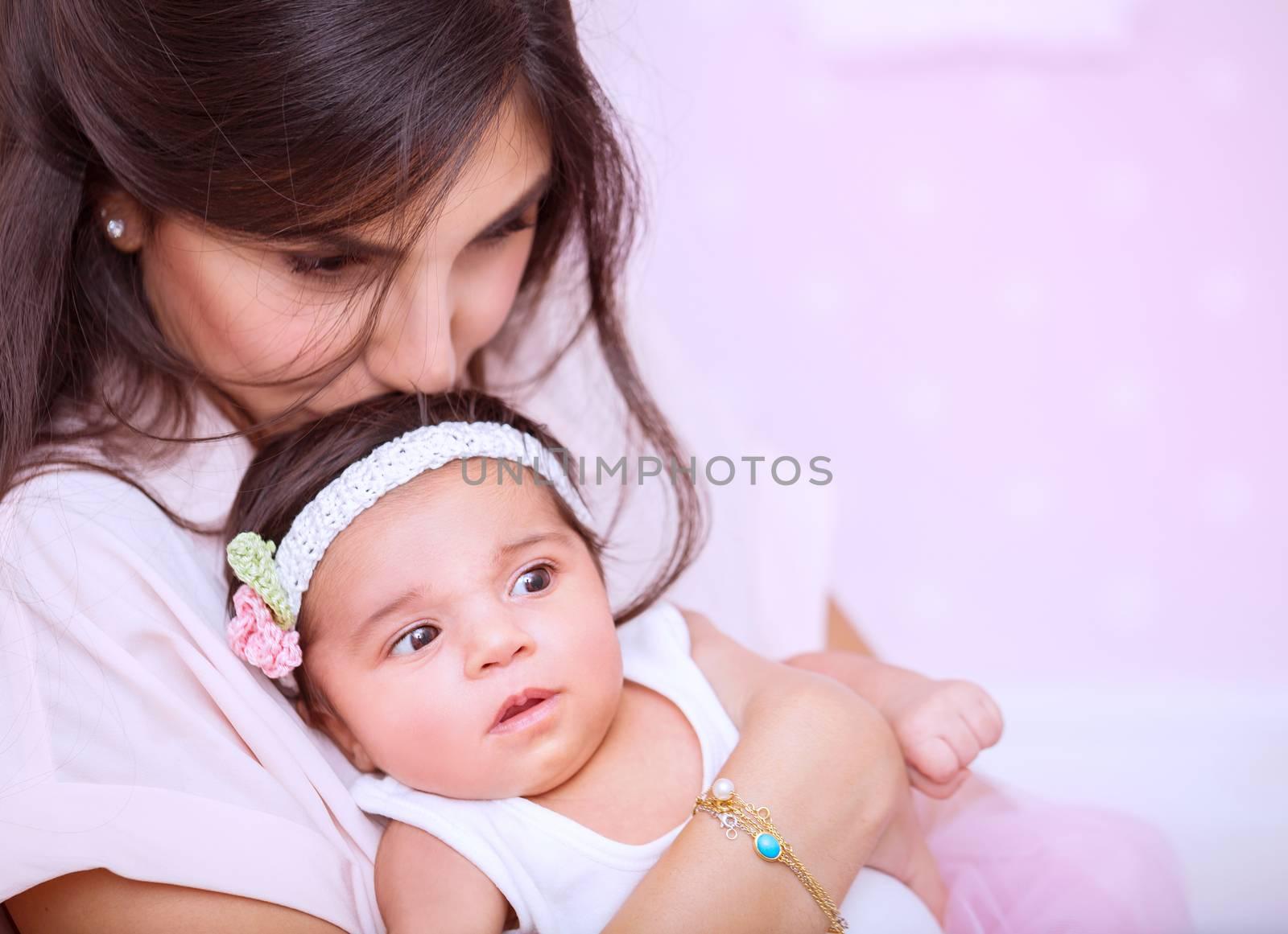 Closeup portrait of beautiful woman with gentleness kissing her cute newborn daughter, enjoying parenthood, mother's love concept