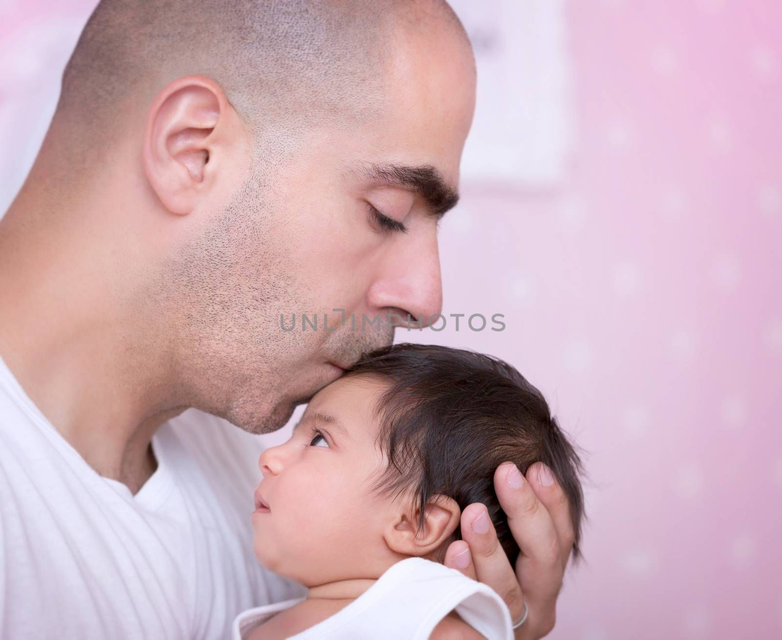 Closeup portrait of a daddy and his baby girl at home, with gentleness kissing his cute newborn daughter, enjoying parenthood, family happiness and father's love concept