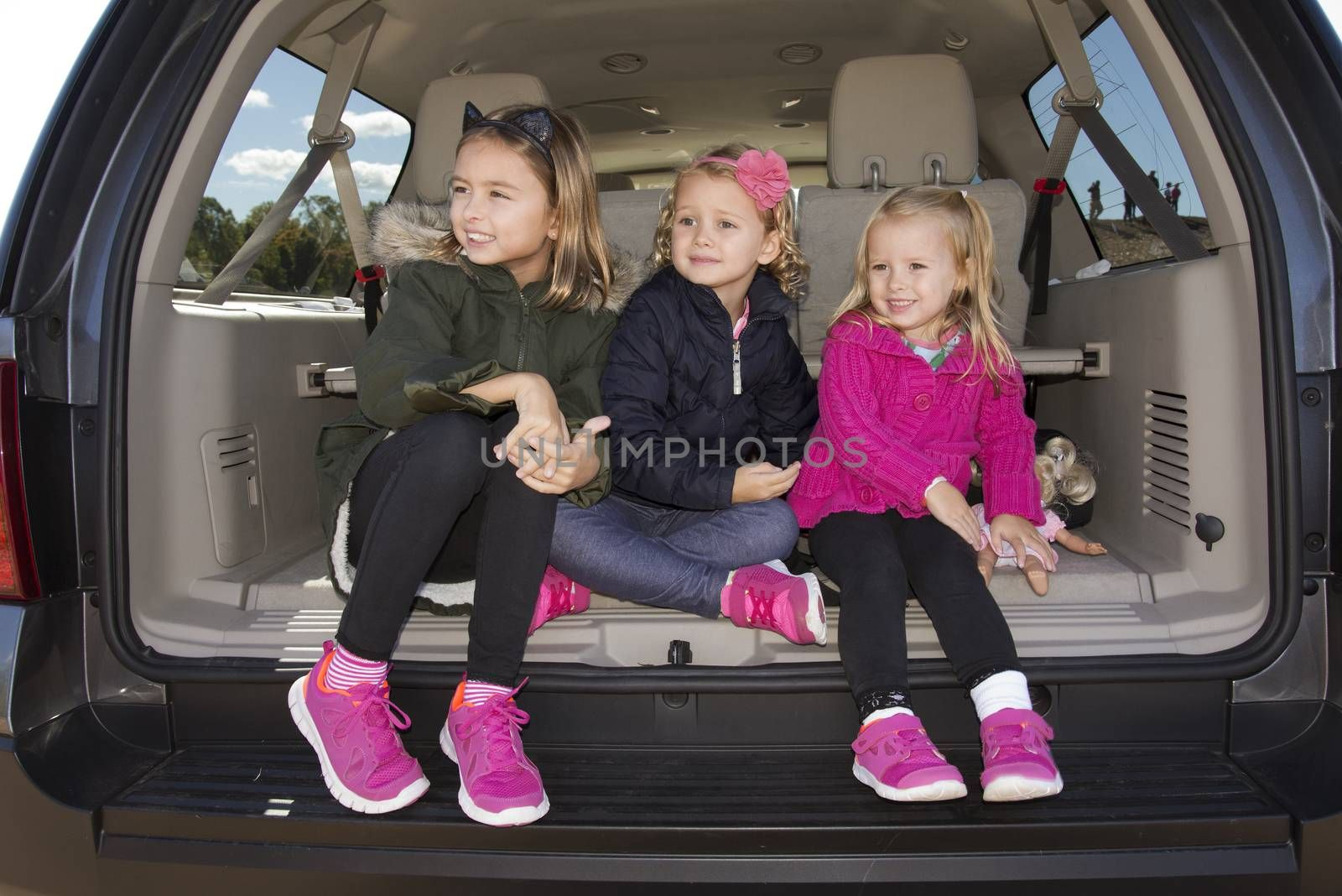 Three young girls sitting in the trunk of a car