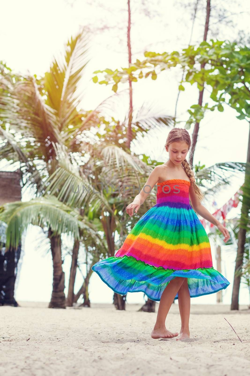 8 years old girl wearing colorful rainbow dress resting on the tropical palm beach in Thailand in summer