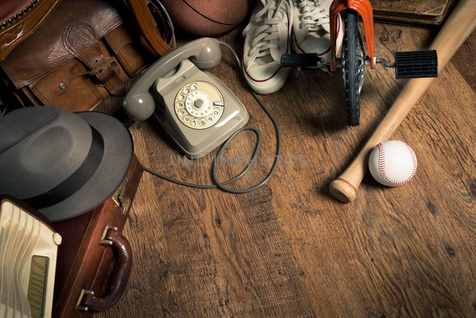 Group of assorted vintage items on hardwood floor at flea market.