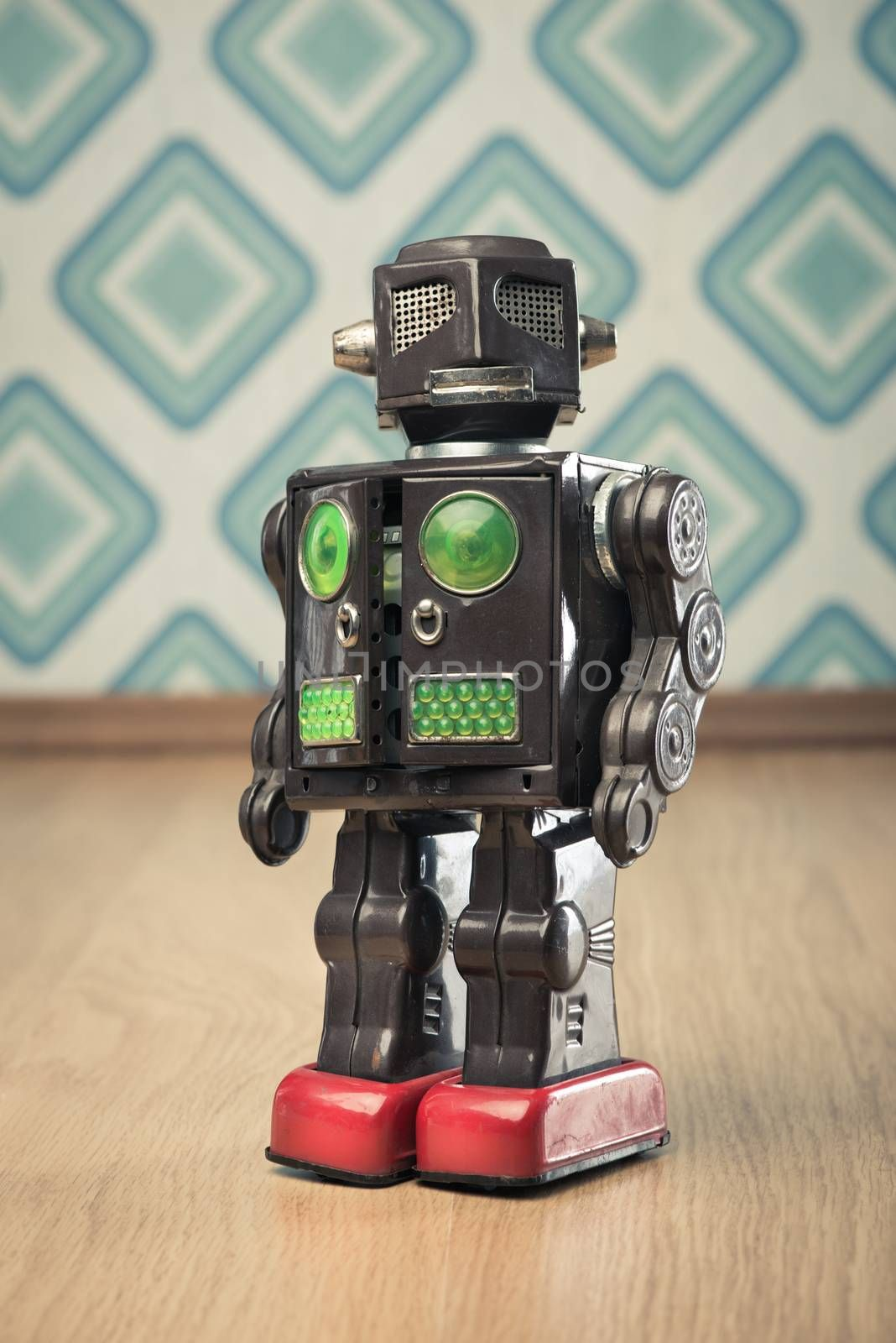 Vintage funny tin toy robot on vintage wallpaper background.