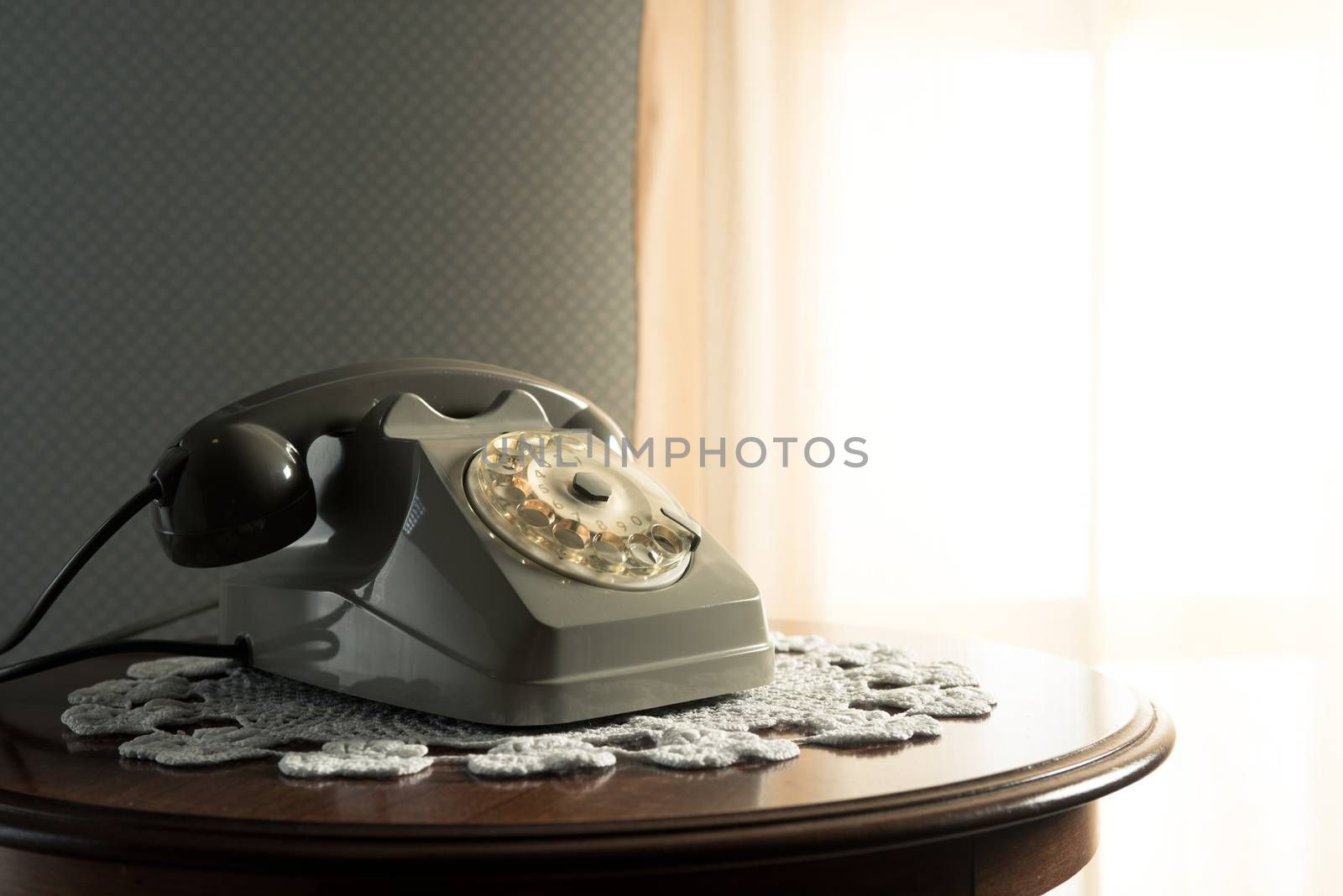 Vintage telephone on doily and wooden table in the living room.