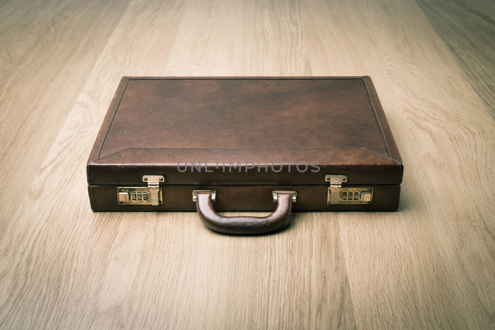Leather vintage briefcase on hardwood floor with safety lock.