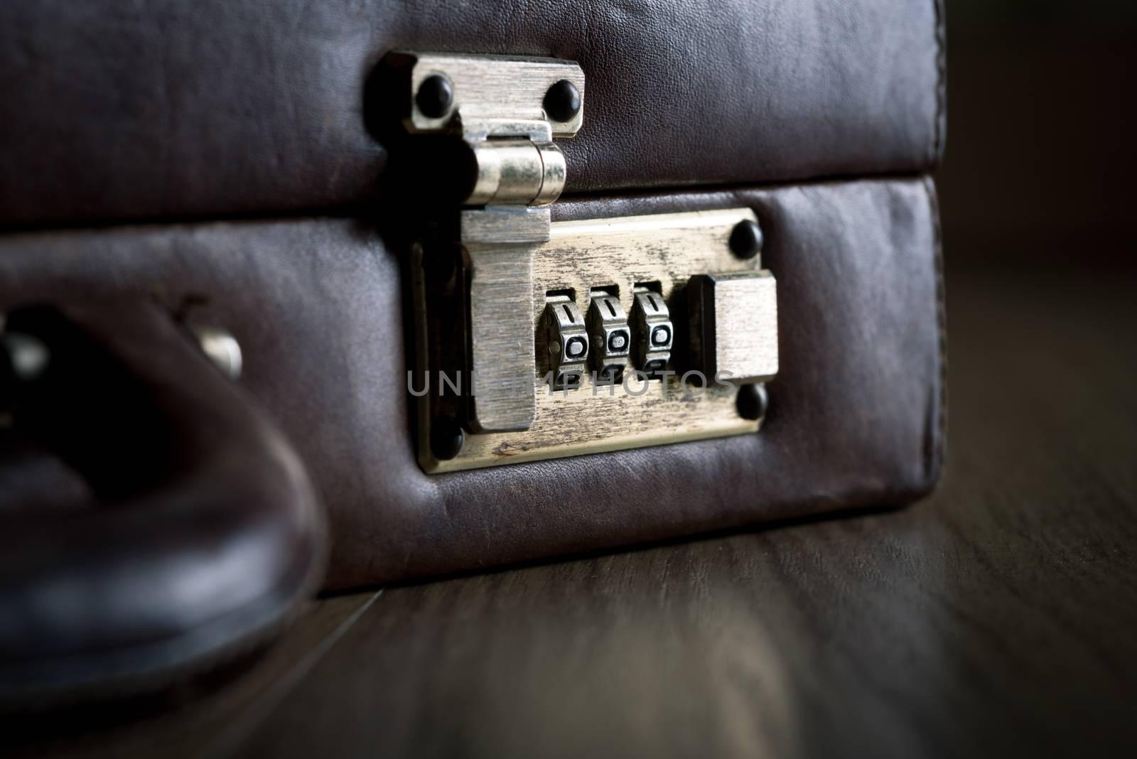 Leather briefcase lock and handle close-up on dark hardwood floor.