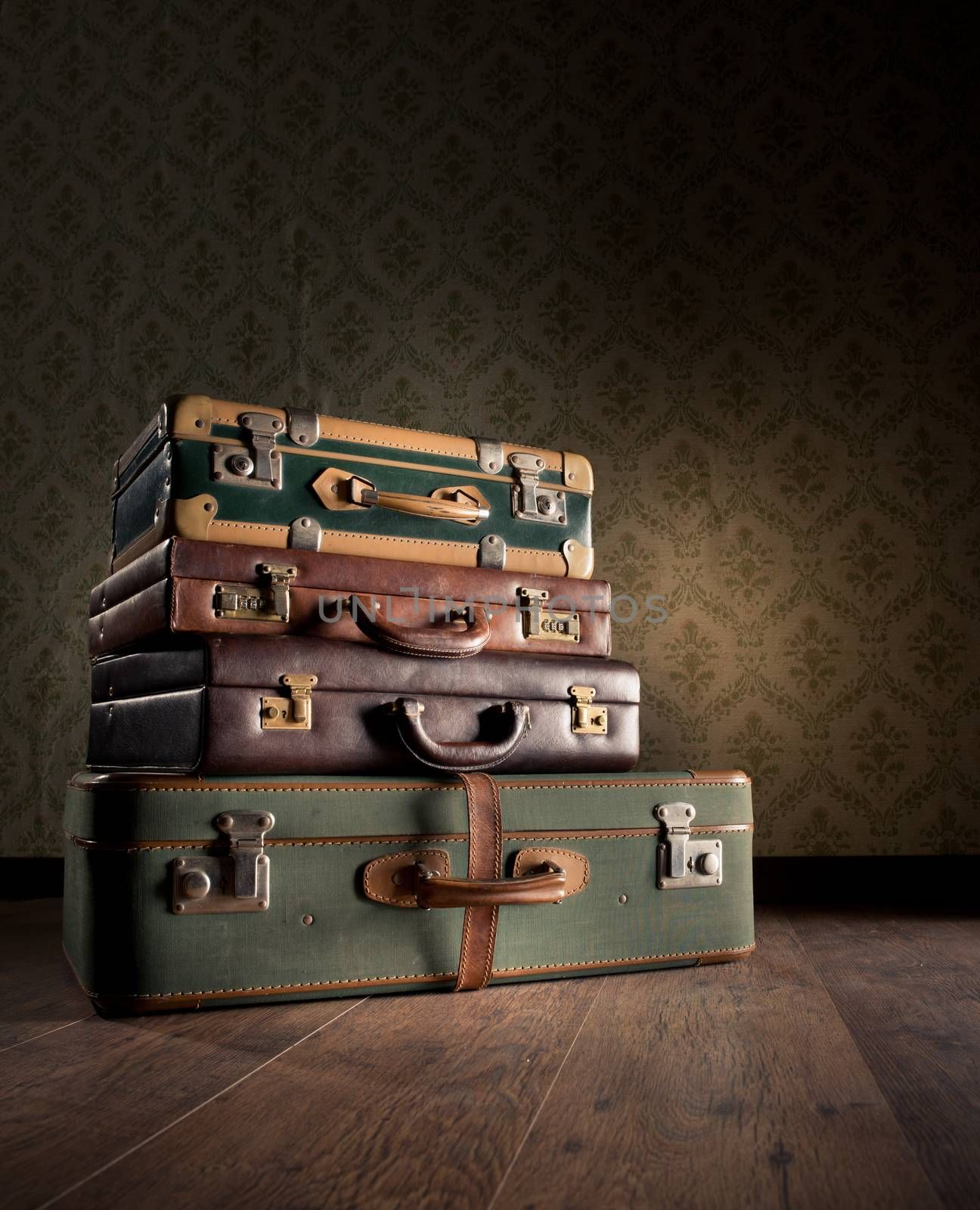 Pile of leather vintage suitcases, retro wallpaper on background.