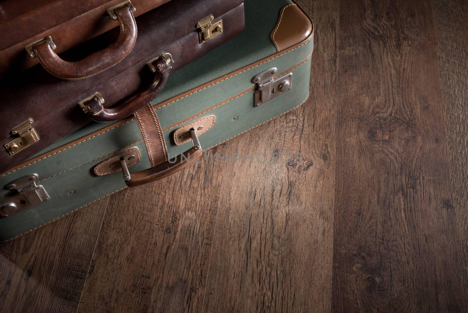 Vintage luggage close-up on dark hardwood floor, travelling concept.