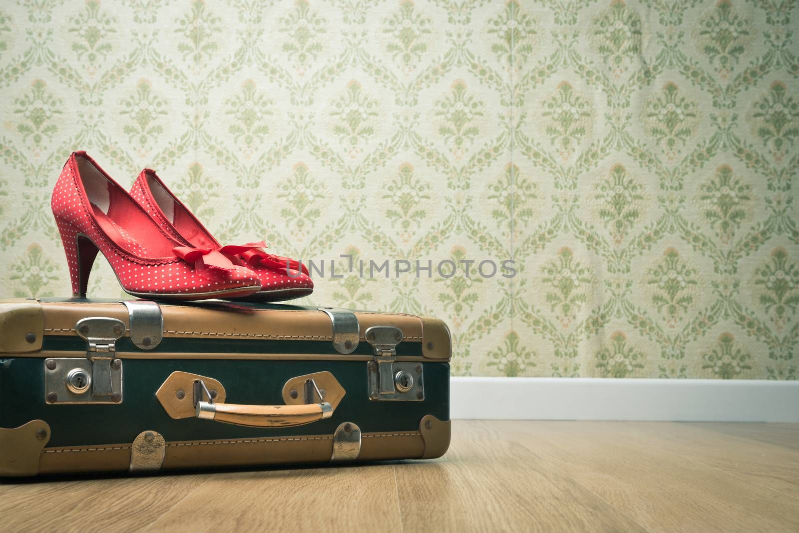 Female red dotted shoes with vintage suitcase on floor and retro wallpaper.
