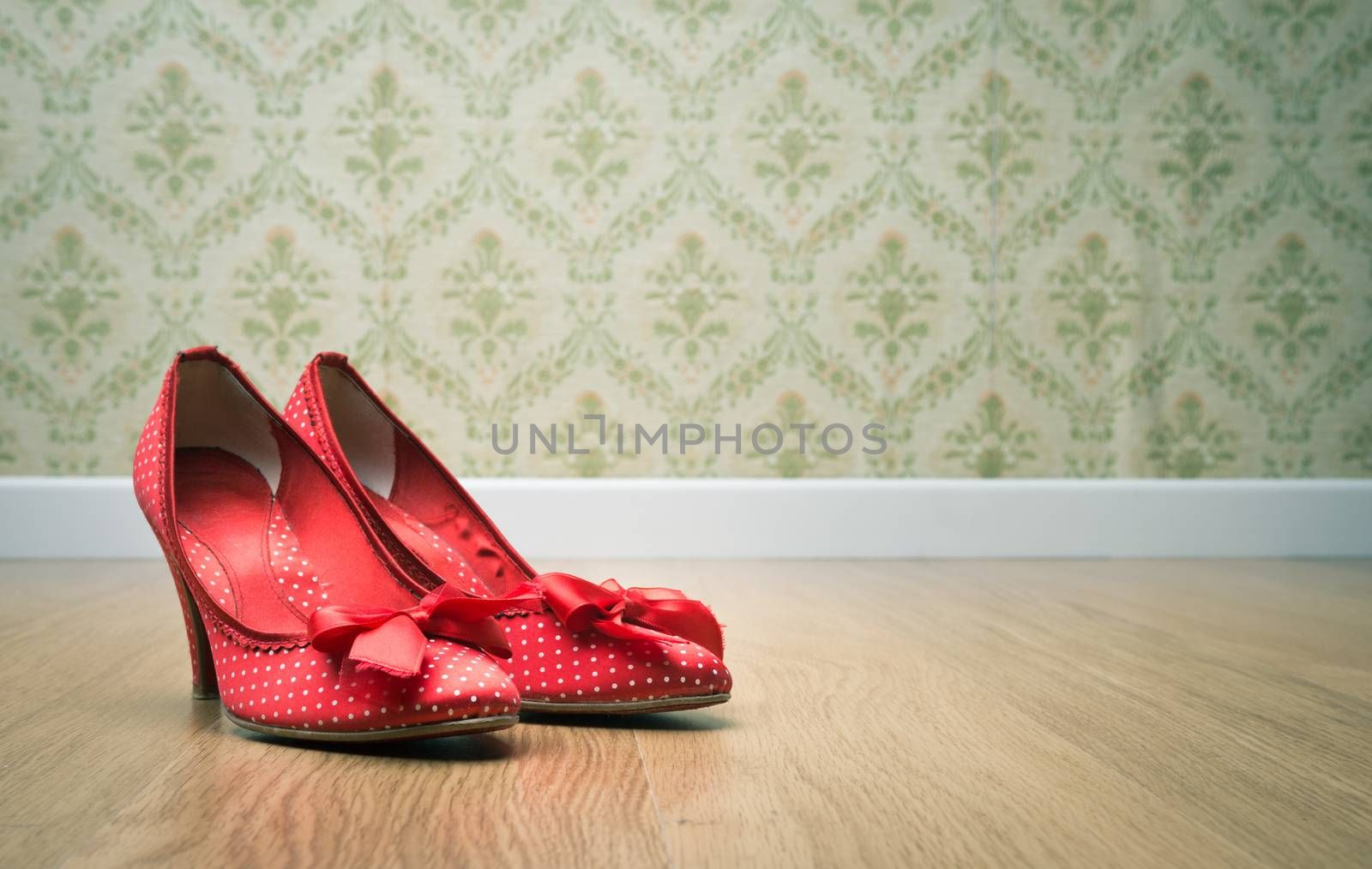 Vintage red dotted female shoes with ribbon on hardwood floor with retro wallpaper on background.