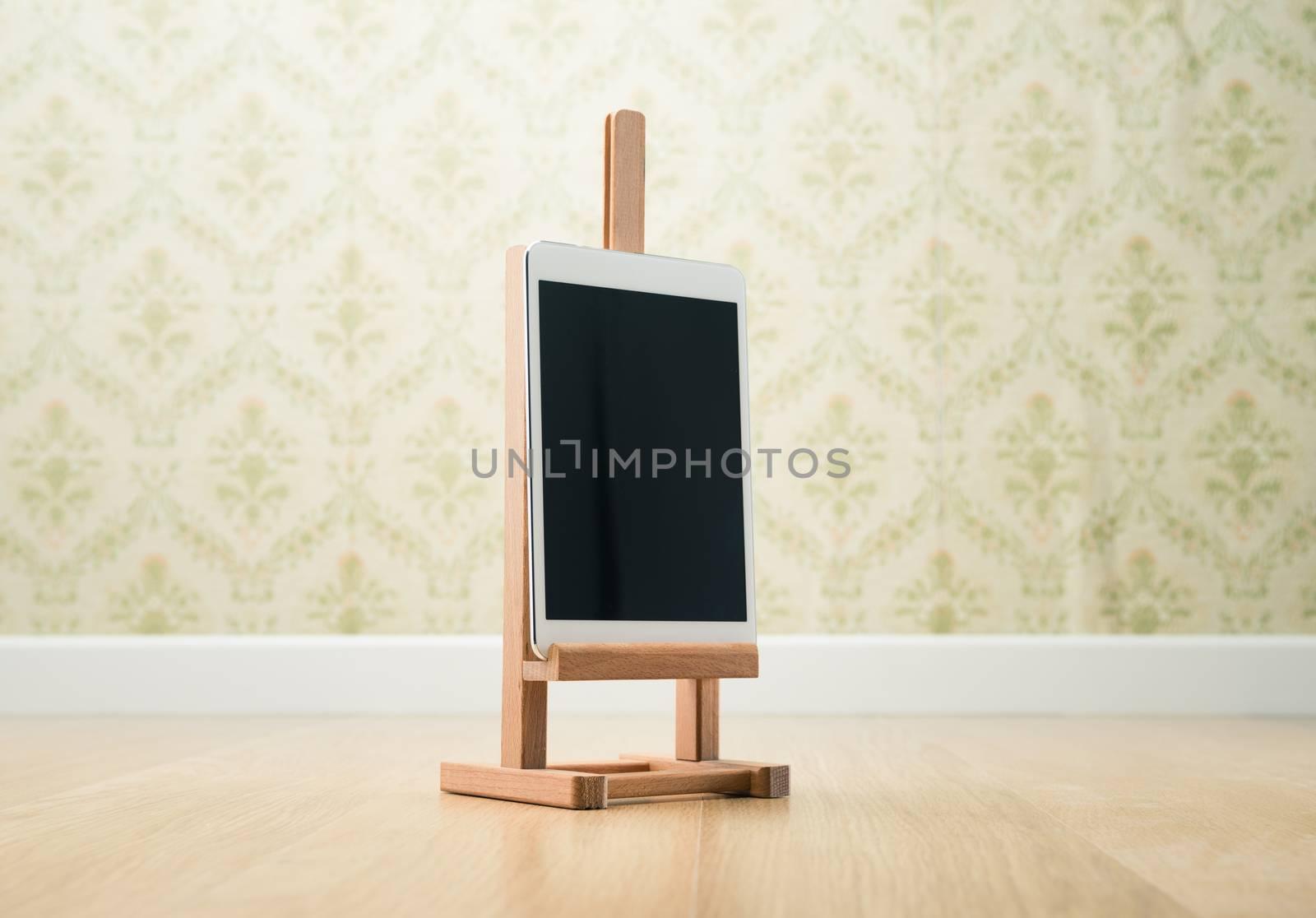 Digital tablet on wooden painting easel, vintage wallpaper on background.
