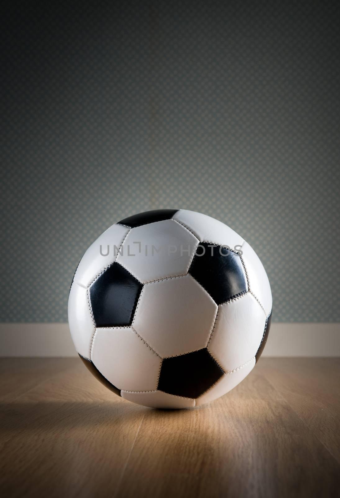 Soccer ball on hardwood floor and vintage wallpaper on background.