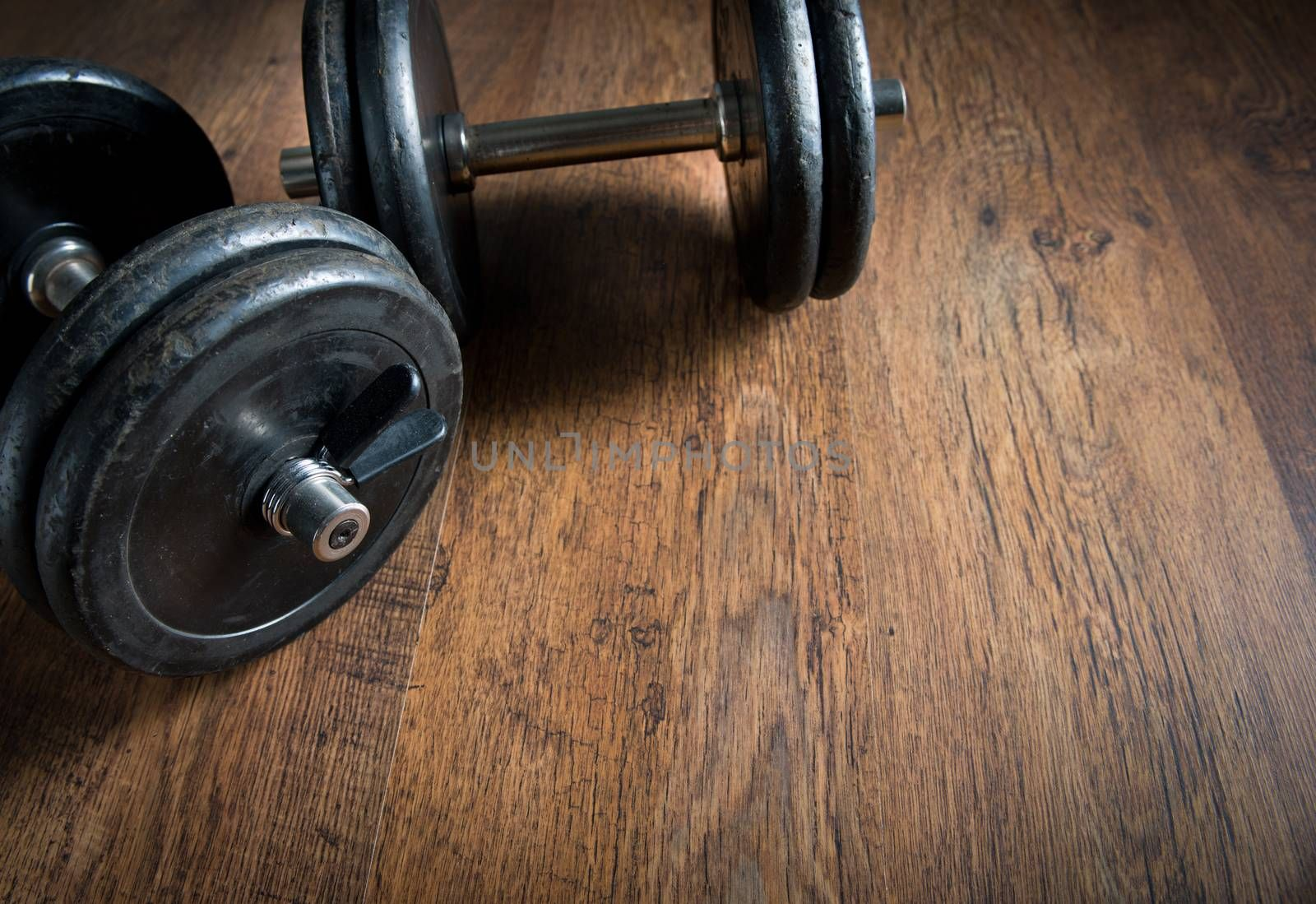 Black barbell weights on dark hardwood floor, weightlifting training concept.