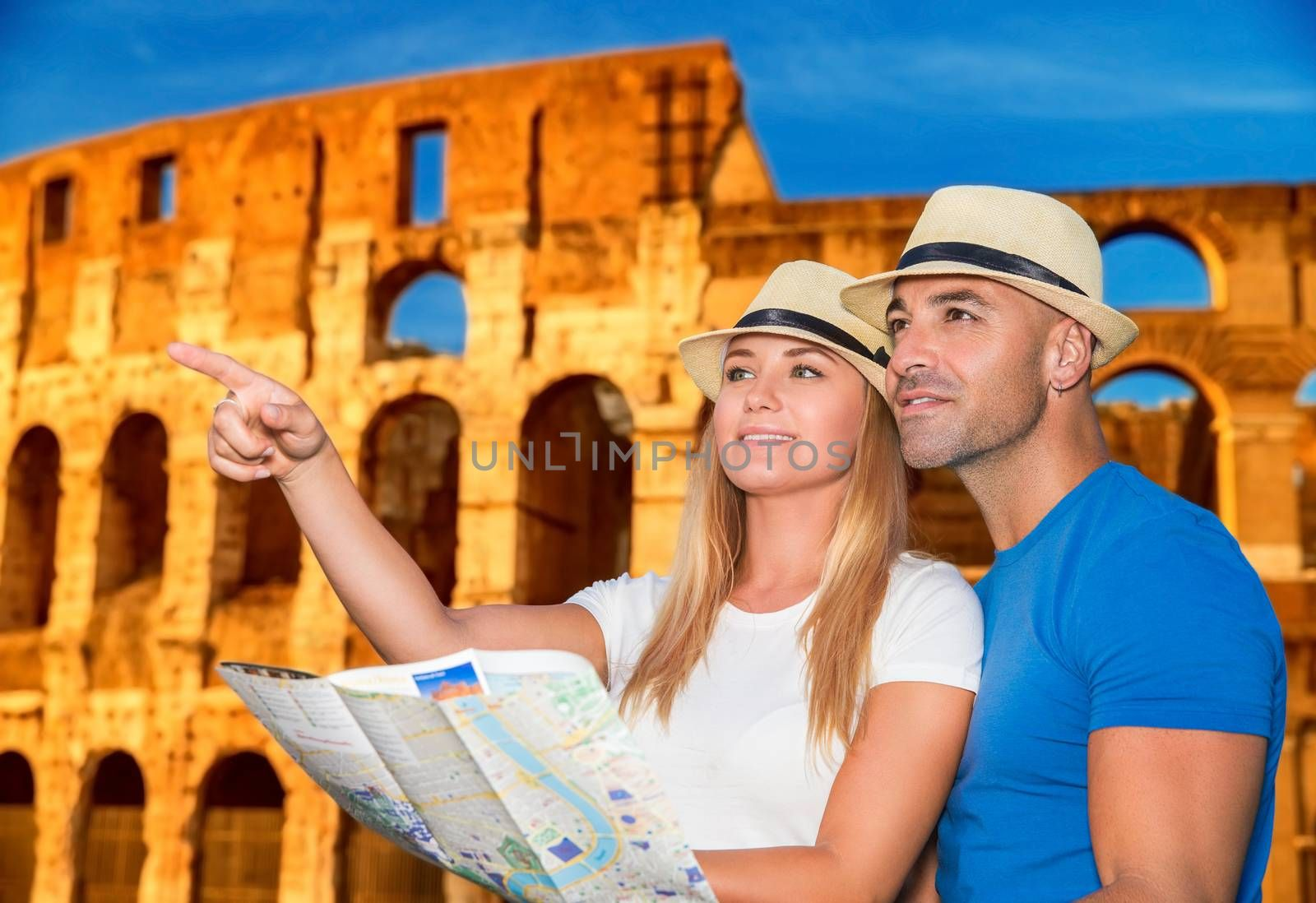 Beautiful active couple with map standing on Coliseum background and looking for right way, travel to Rome and exploring it by themself, Italy Europe
