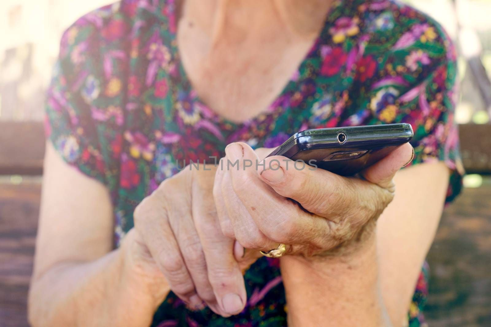 Selective focus on the old female fingers on cell phone
